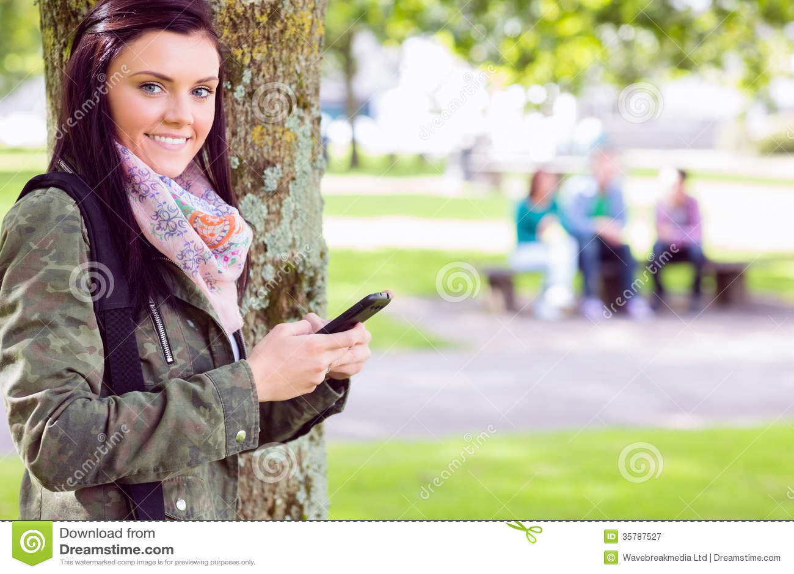 Invio di messaggi di testo della studentessa di college con gli studenti vaghi in parco
