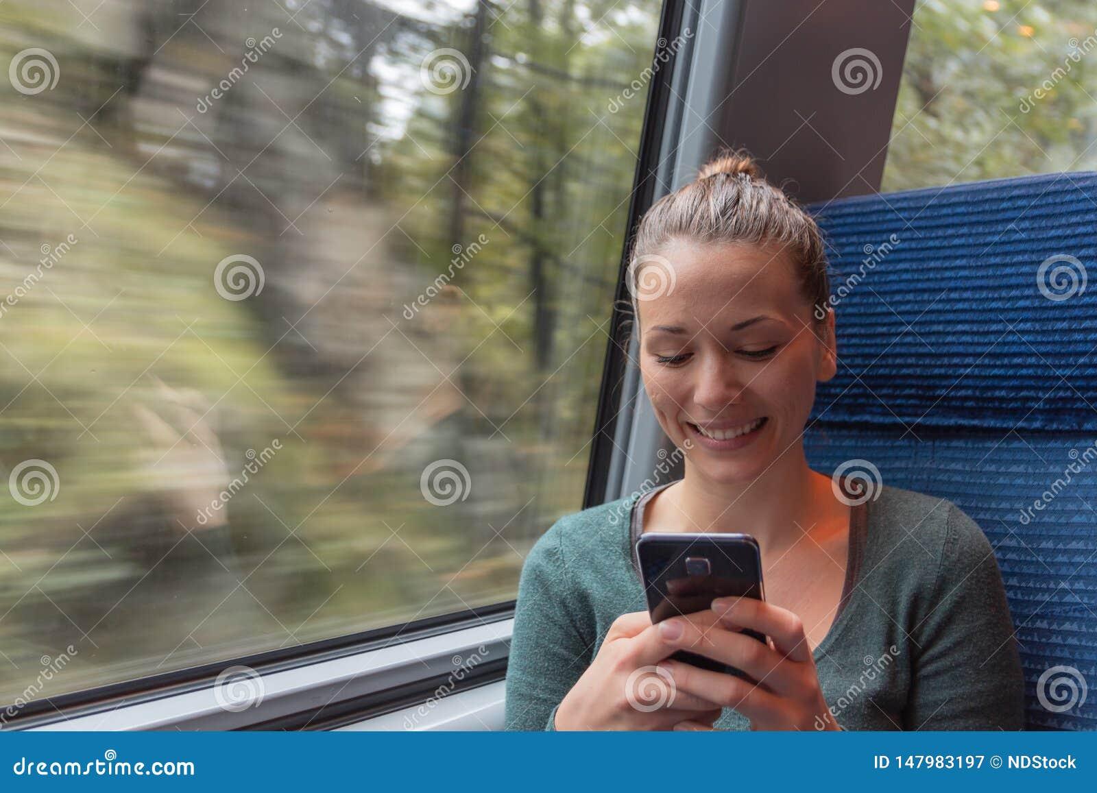 Invio di messaggi di testo della giovane donna con il suo smartphone durante il viaggio nel treno mentre sta andando lavorare