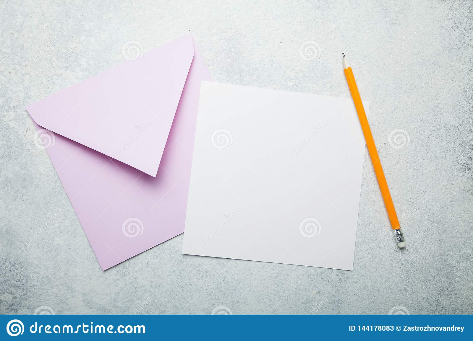 Invitation letter or postcard. An empty square piece of paper with space for text, a pink envelope and a pencil on a vintage white