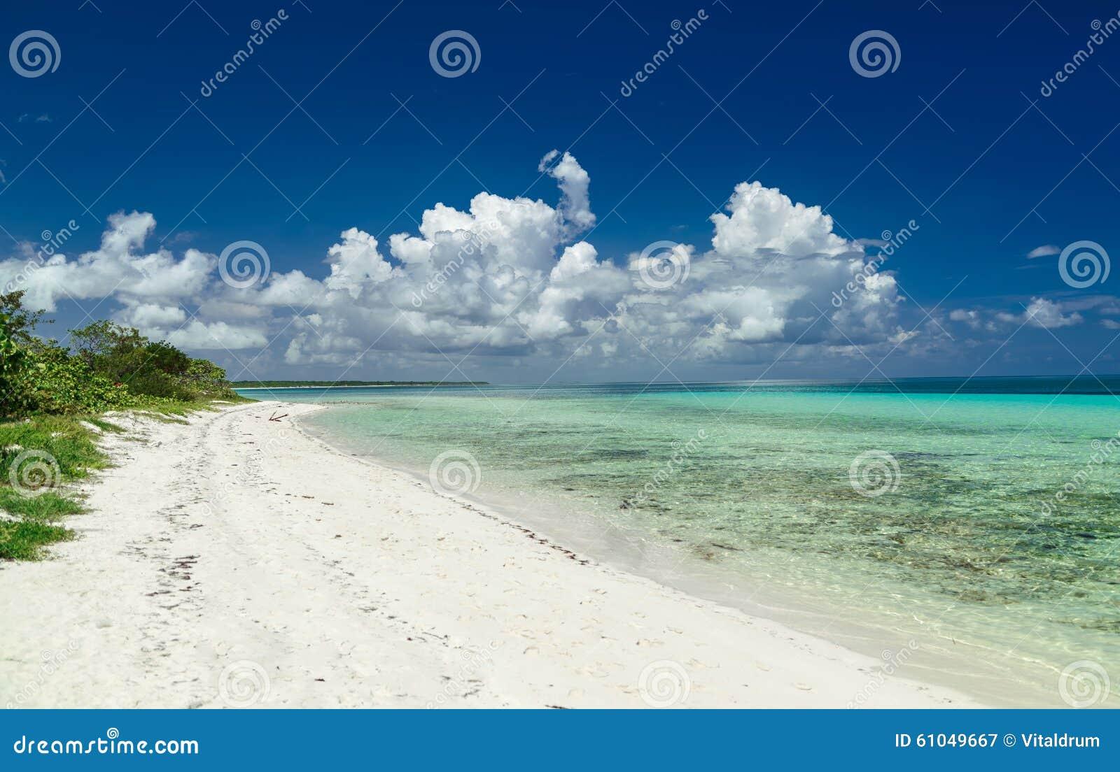 Inviterande fantastisk naturlig landskapsikt av den kubanska stranden mot djupblå himmel och stillsamt, turkoshav
