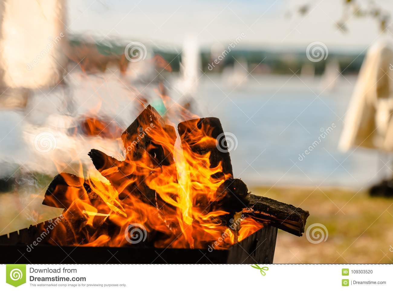 Inviting bonfire on the beach of the reservoir with yachts, people during the summer, bring back memories