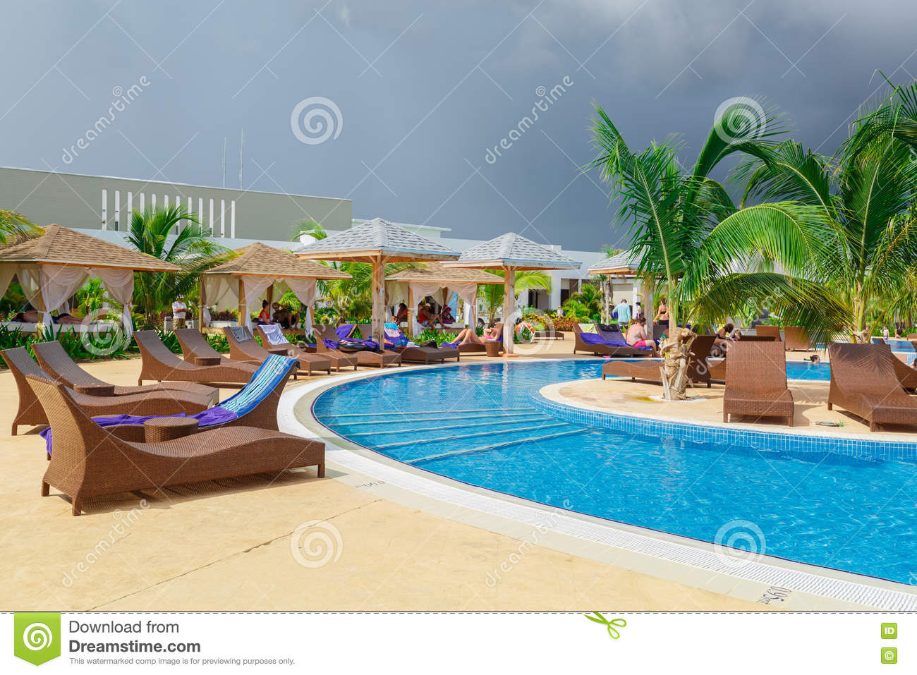 Inviting view of a curved wide open comfortable swimming pool with people relaxing and enjoying their time