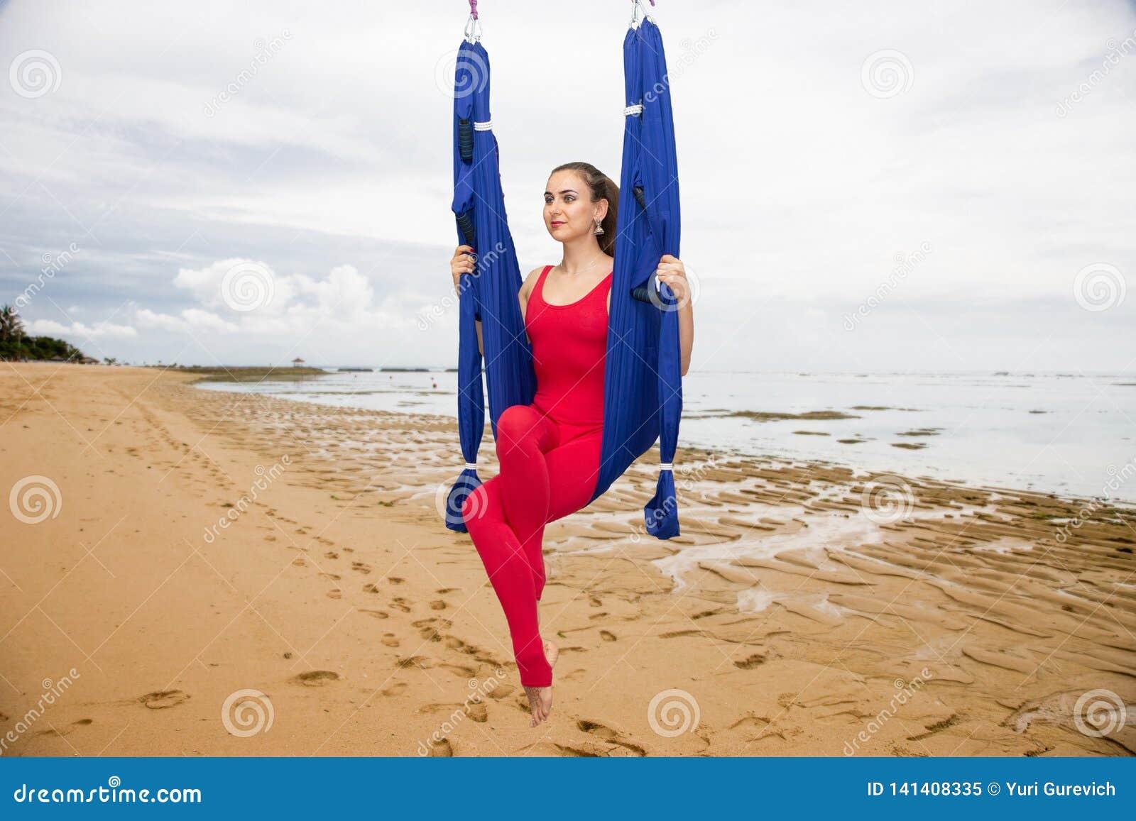 Ioga aérea ou ioga antigravitante Asana praticando da ioga da mosca da jovem mulher fora