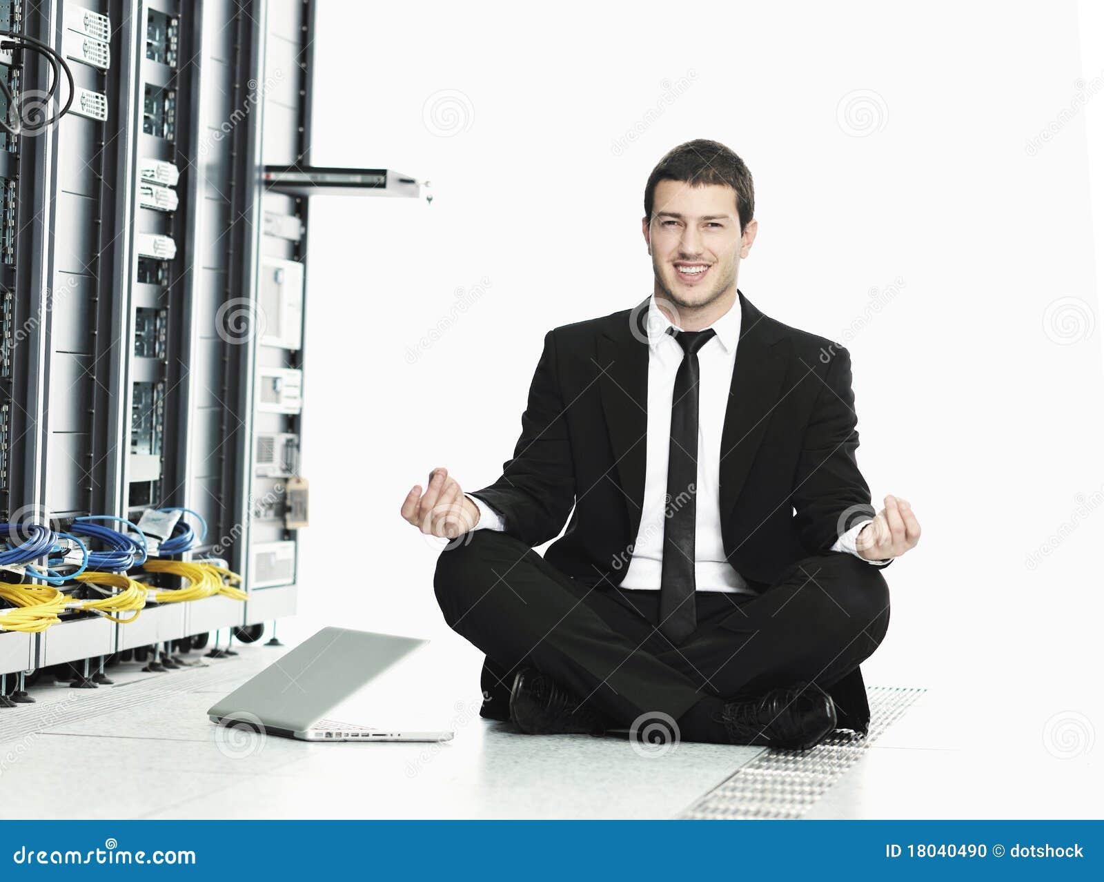 Ioga da prática do homem de negócio no quarto do server de rede