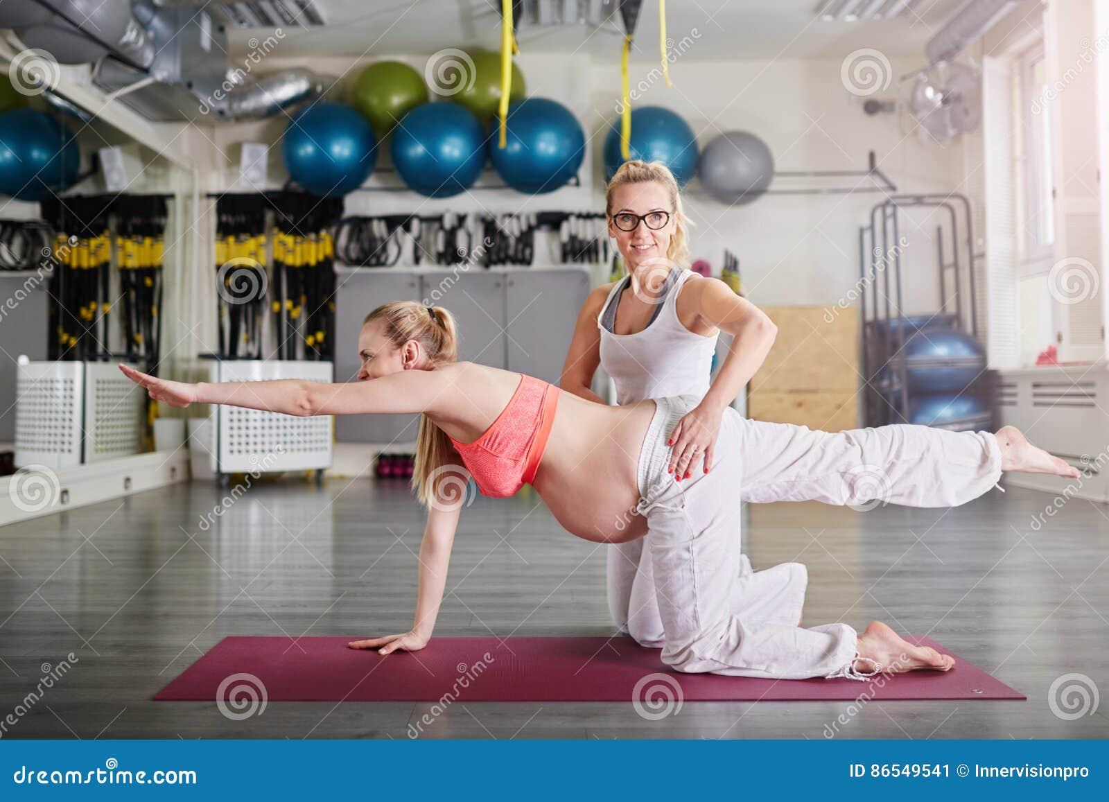 Ioga do treinamento da mulher gravida fixada pelo instrutor pessoal