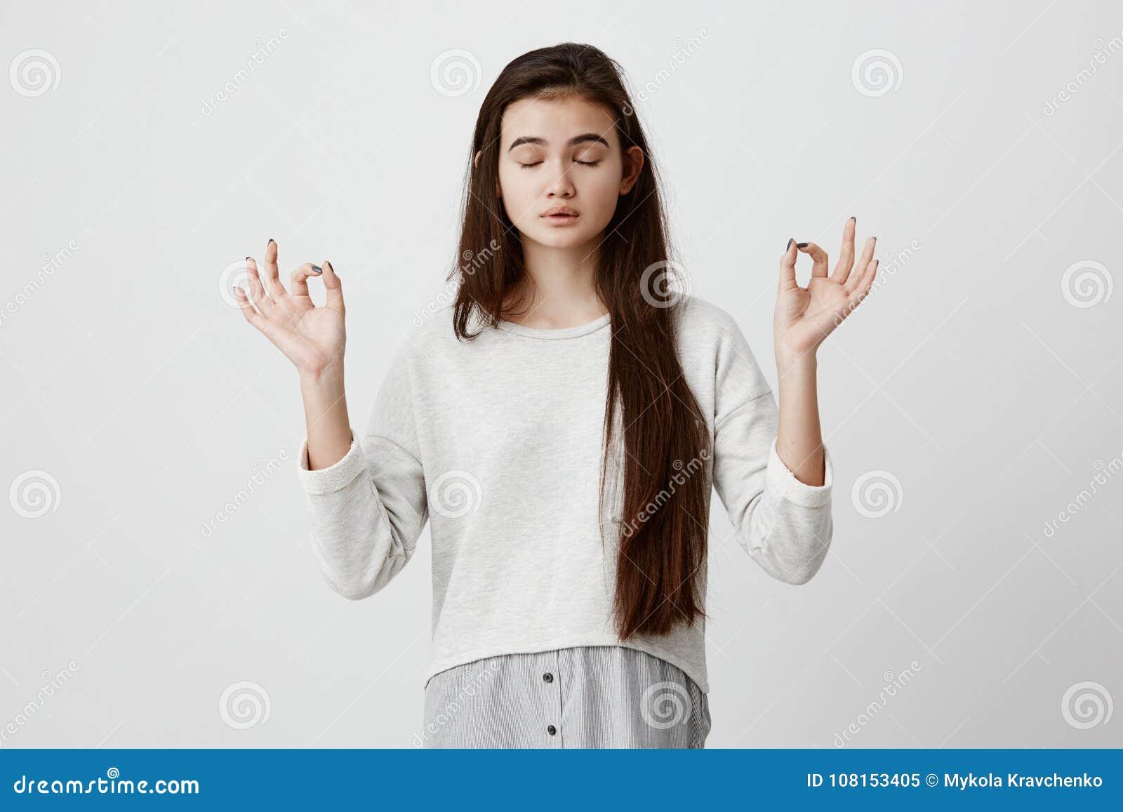 Ioga e meditação Menina moreno ocasionalmente vestida bonita que mantém os olhos fechados ao meditar, sentindo relaxado