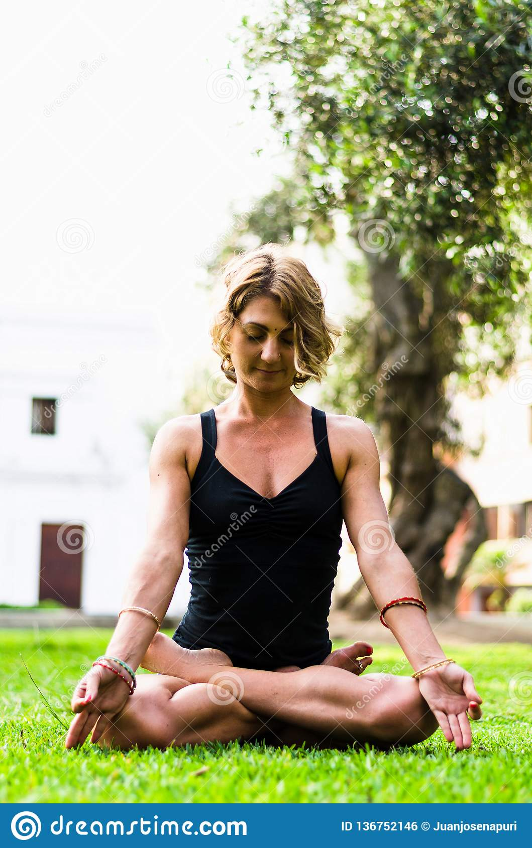 Ioga meditando e praticando da mulher, Padmasana Meditação em Sunny Autumn Day At Park Exercício ao ar livre