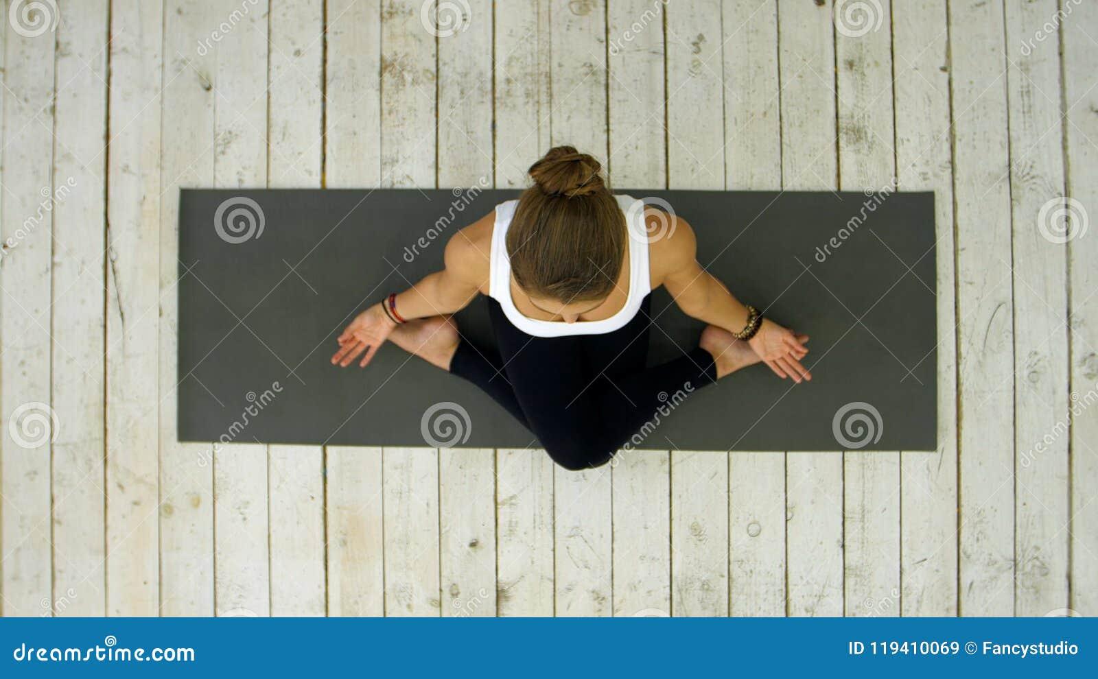 Ioga praticando da jovem mulher bonita desportiva, sentando-se na posição equipada com pernas transversal