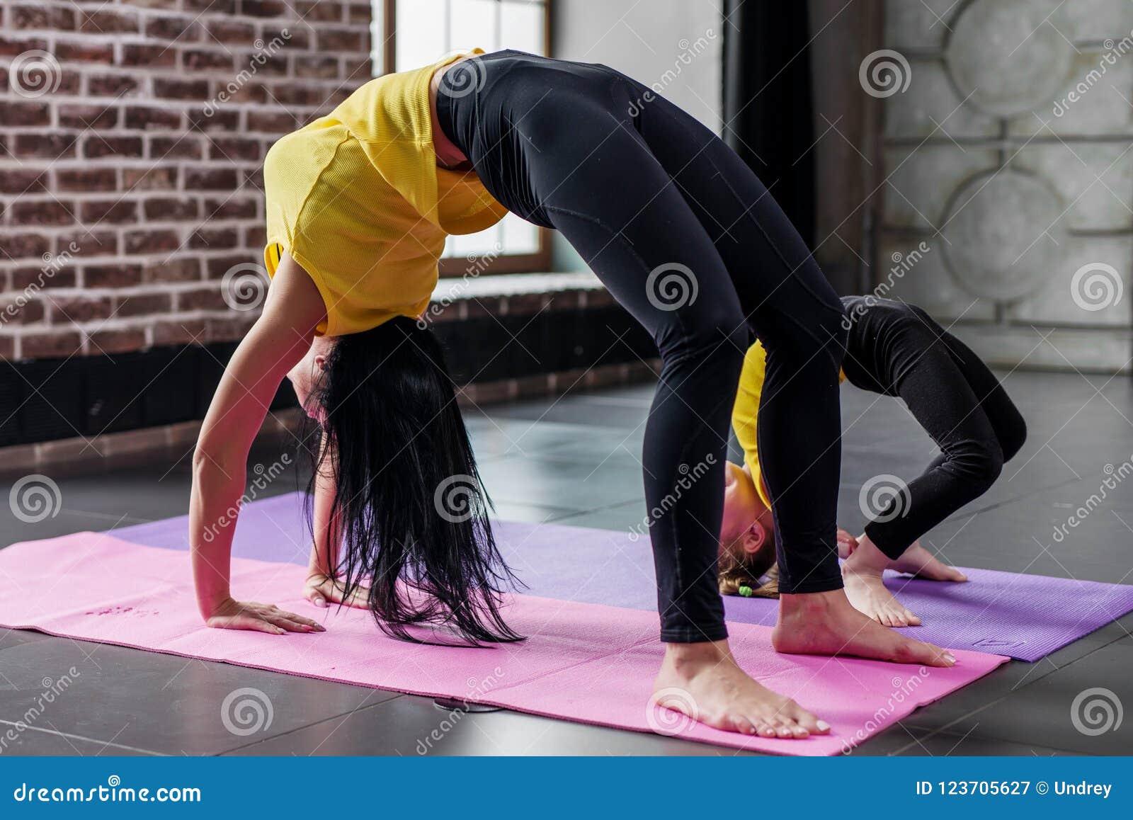 Ioga praticando da menina da mulher e da criança junto em casa, estando na pose da ponte