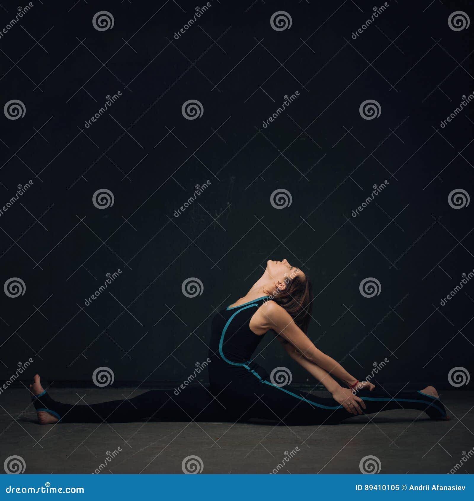 Ioga praticando da mulher contra uma parede escura