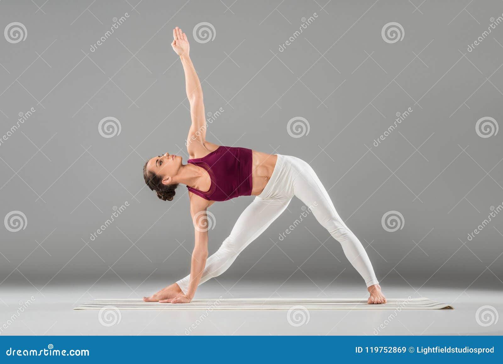 Ioga praticando da mulher, estando em exercício prolongado do ângulo lateral, Utthita