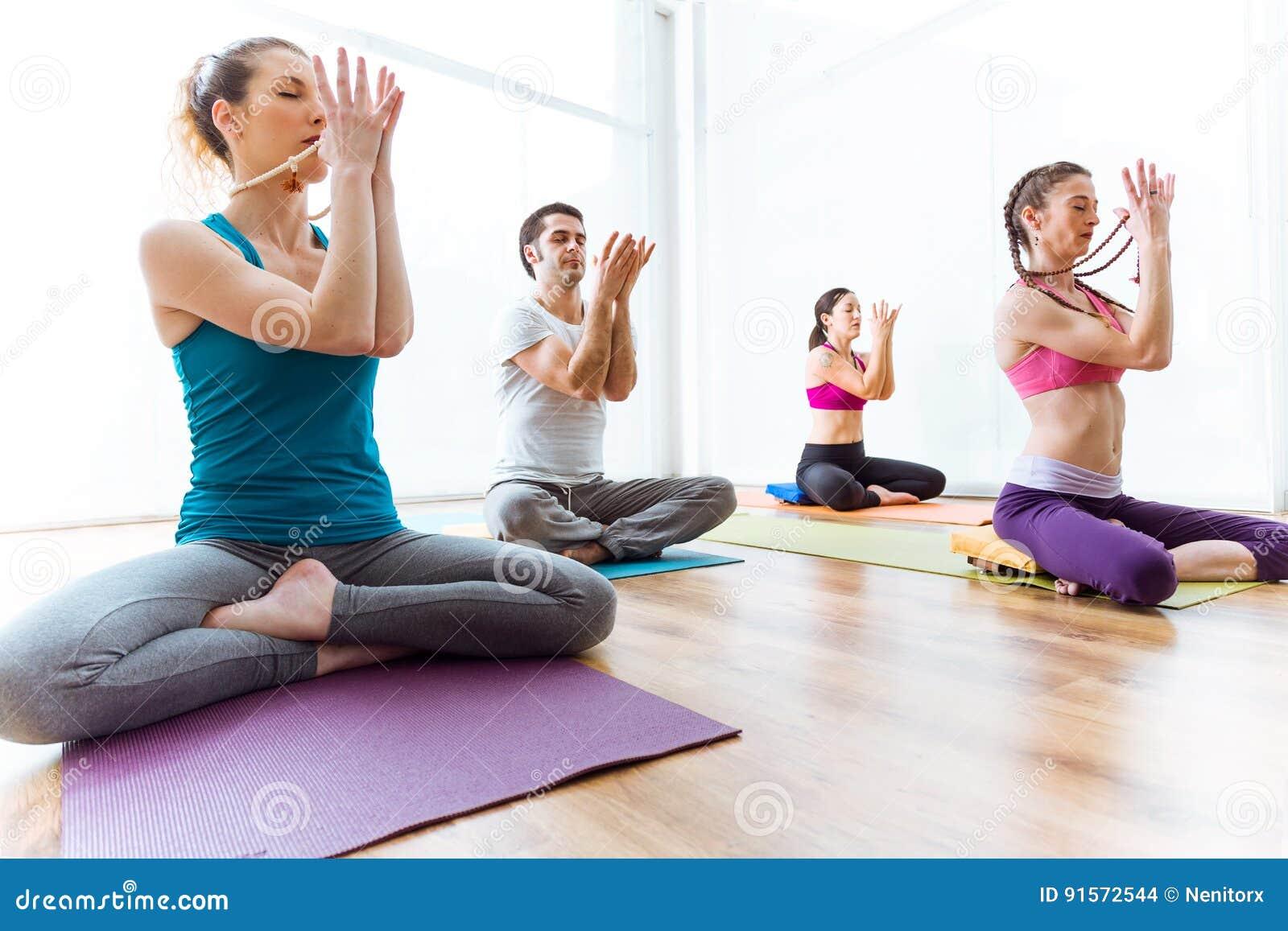 Ioga praticando do grupo de pessoas em casa na posição de lótus