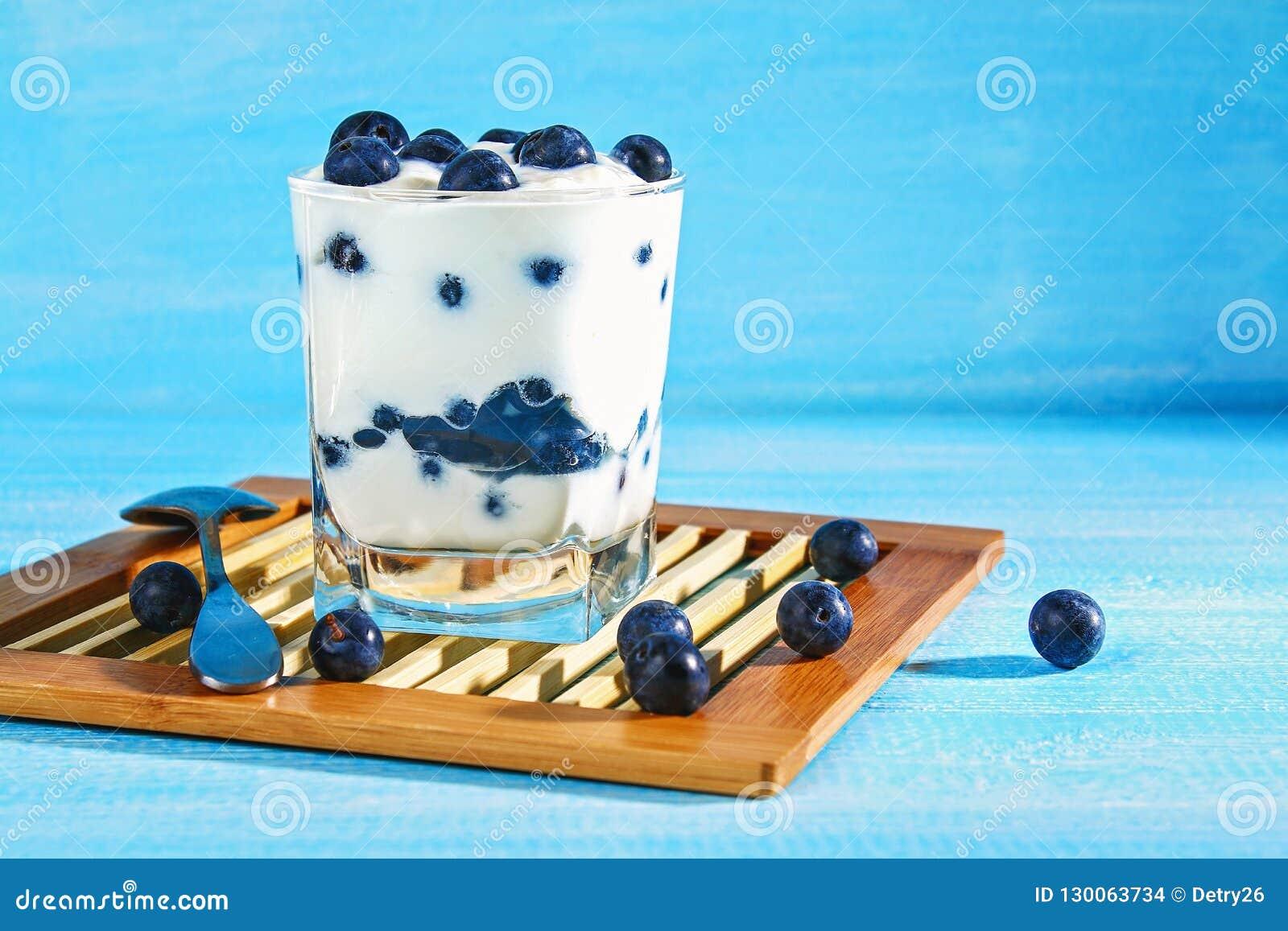 Iogurte com as bagas azuis da ameixoeira-brava em um vidro Framboesa do gelado da baga dessert