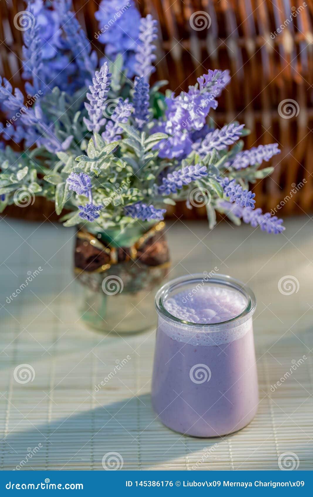 Iogurte de mirtilo nos frascos de vidro na tabela de madeira no ver?o Iogurte doce do leite caseiro com uva-do-monte