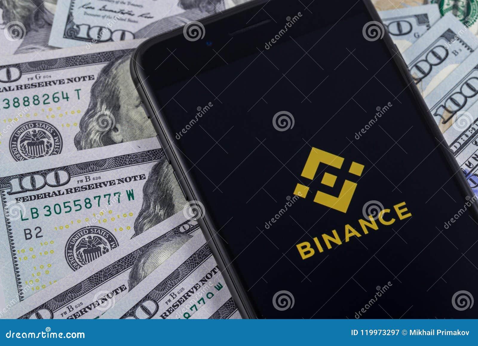 IPhone de Apple e logotipo de Binance, e dólares Binance é um cryptoc