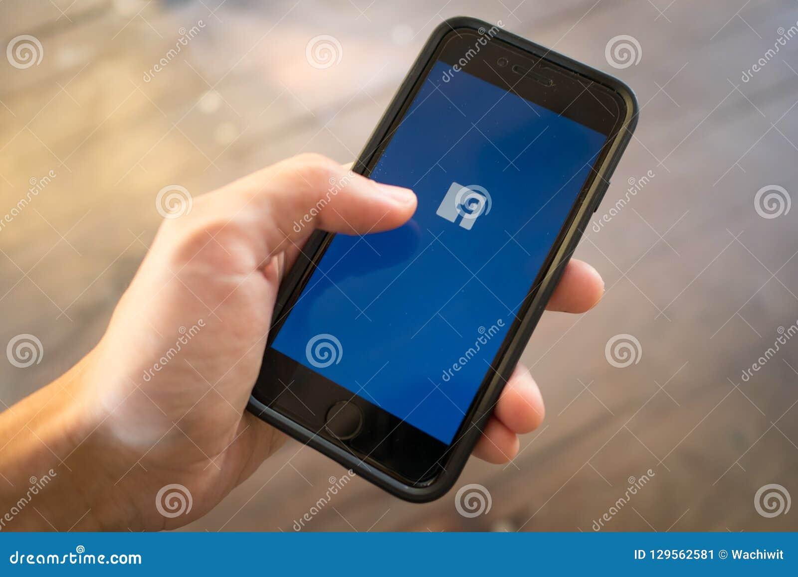 IPhone 7 trzymający w jeden ręce pokazuje swój ekran z Facebook logo
