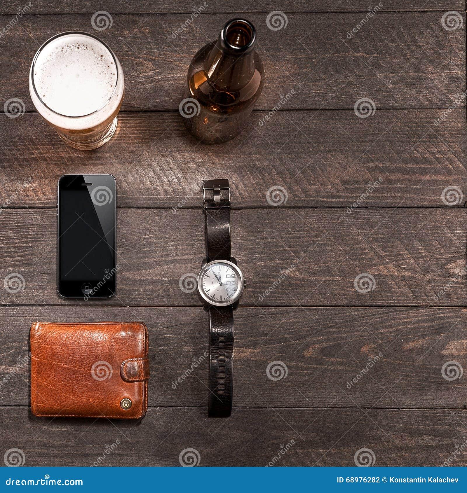 Iphone y vidrio de la cerveza de relojes cerca en de madera
