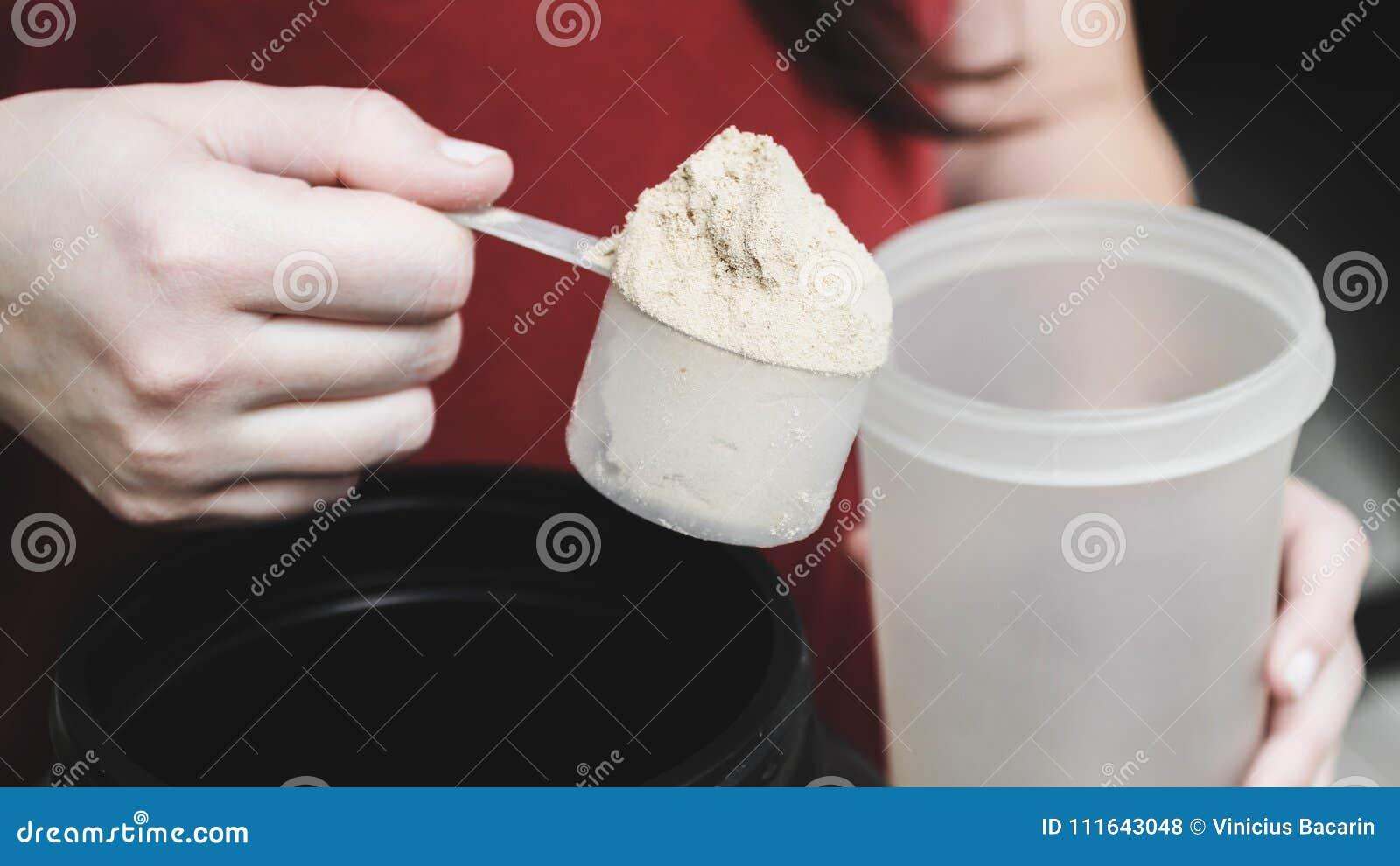 Ir derramar o pó da proteína da caseína no copo