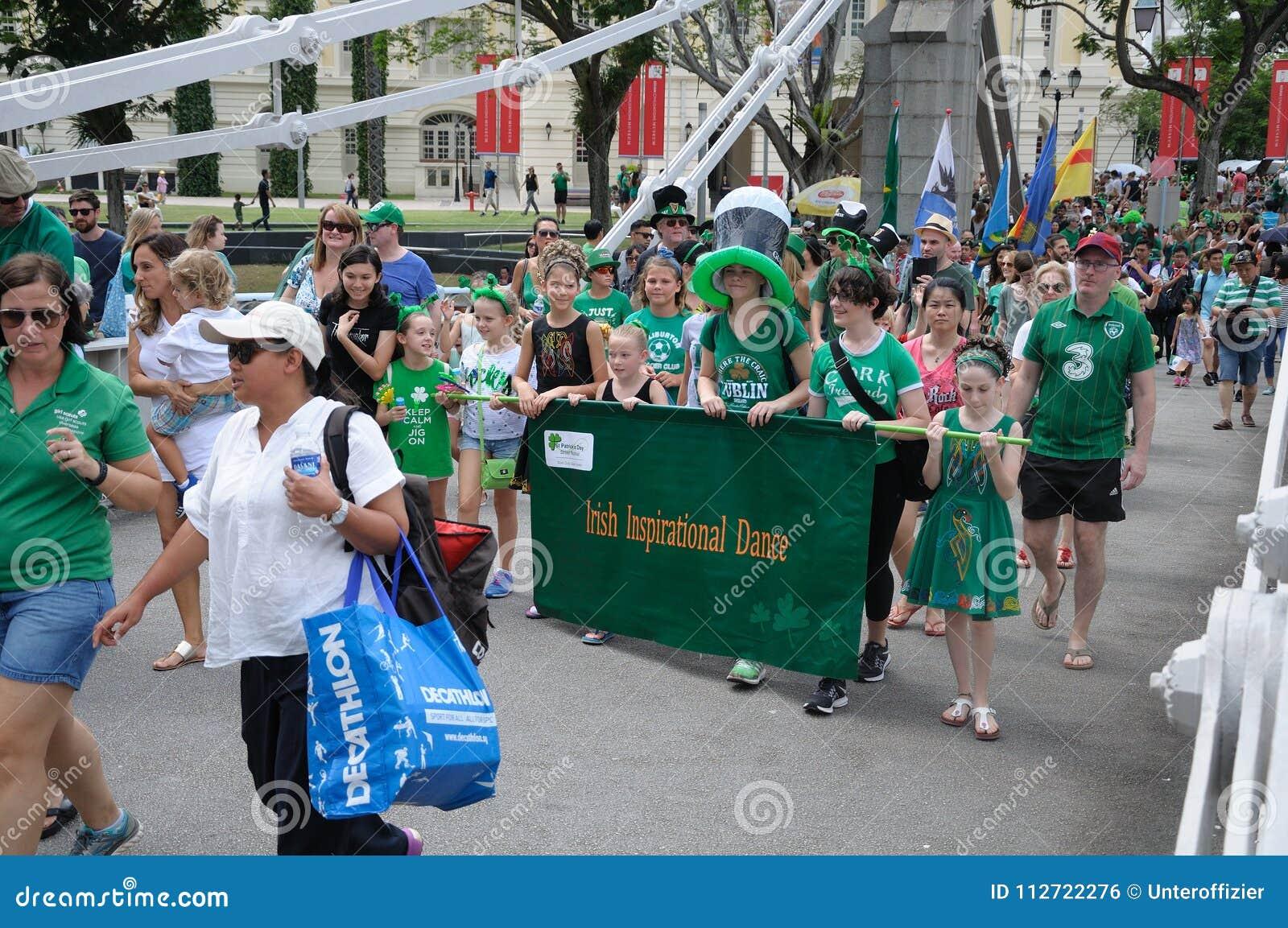 Irische inspirierend Tanz-Gruppe paraders, welche die Cavengah-Brücke in Singapur während des St- Patrick` s Tages 2018 kreuzen