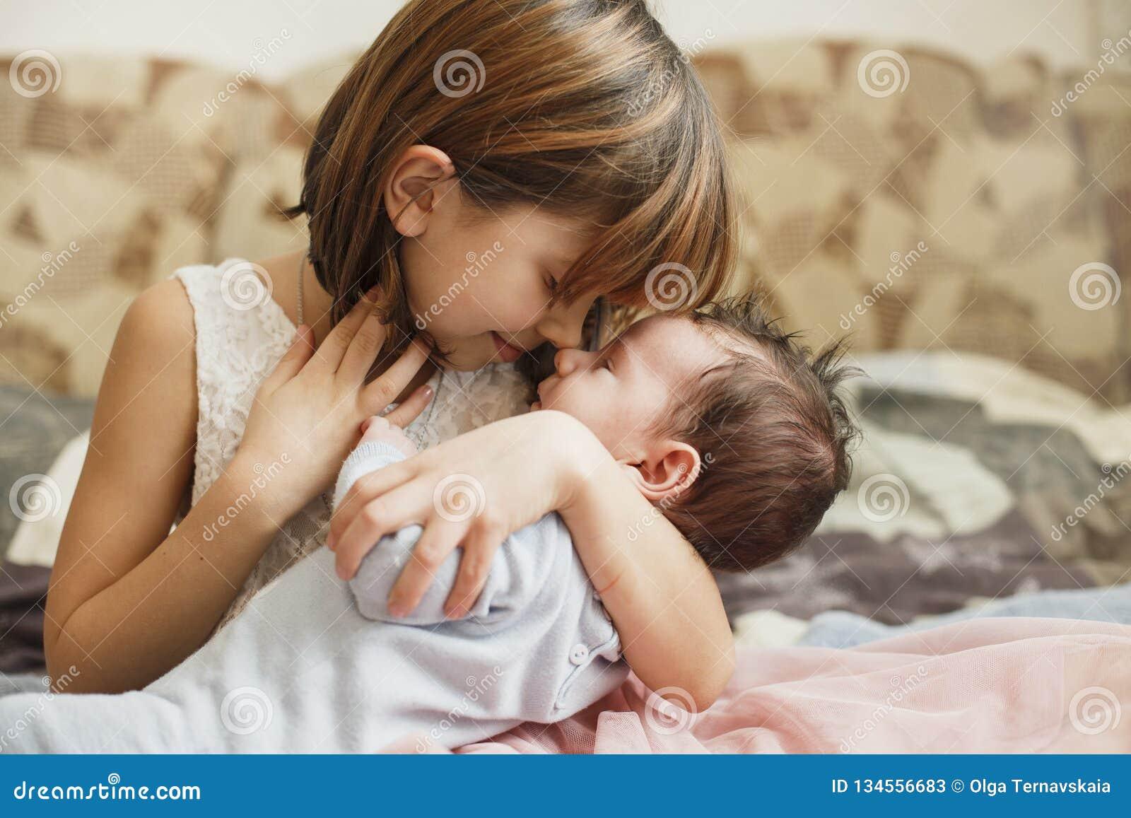 Irmã mais nova que abraça seu irmão recém-nascido Criança da criança que encontra o irmão novo A menina bonito e o bebê recém-nas