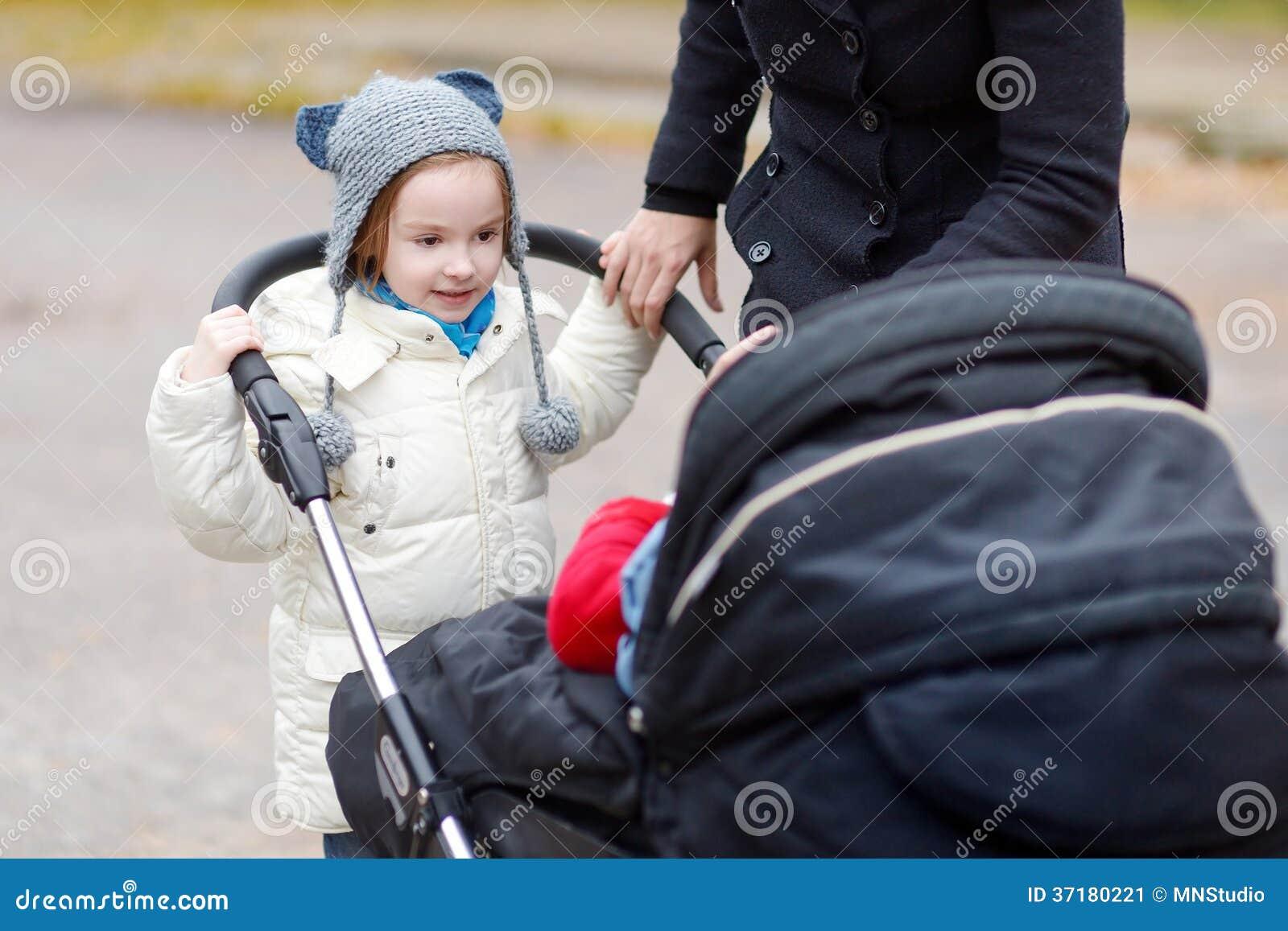 Irmã mais nova que empurra um carrinho de criança com seu irmão