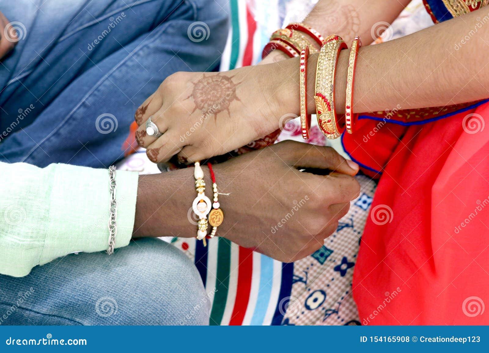 Irmã nova indiana que amarra o rakhi no pulso do irmão