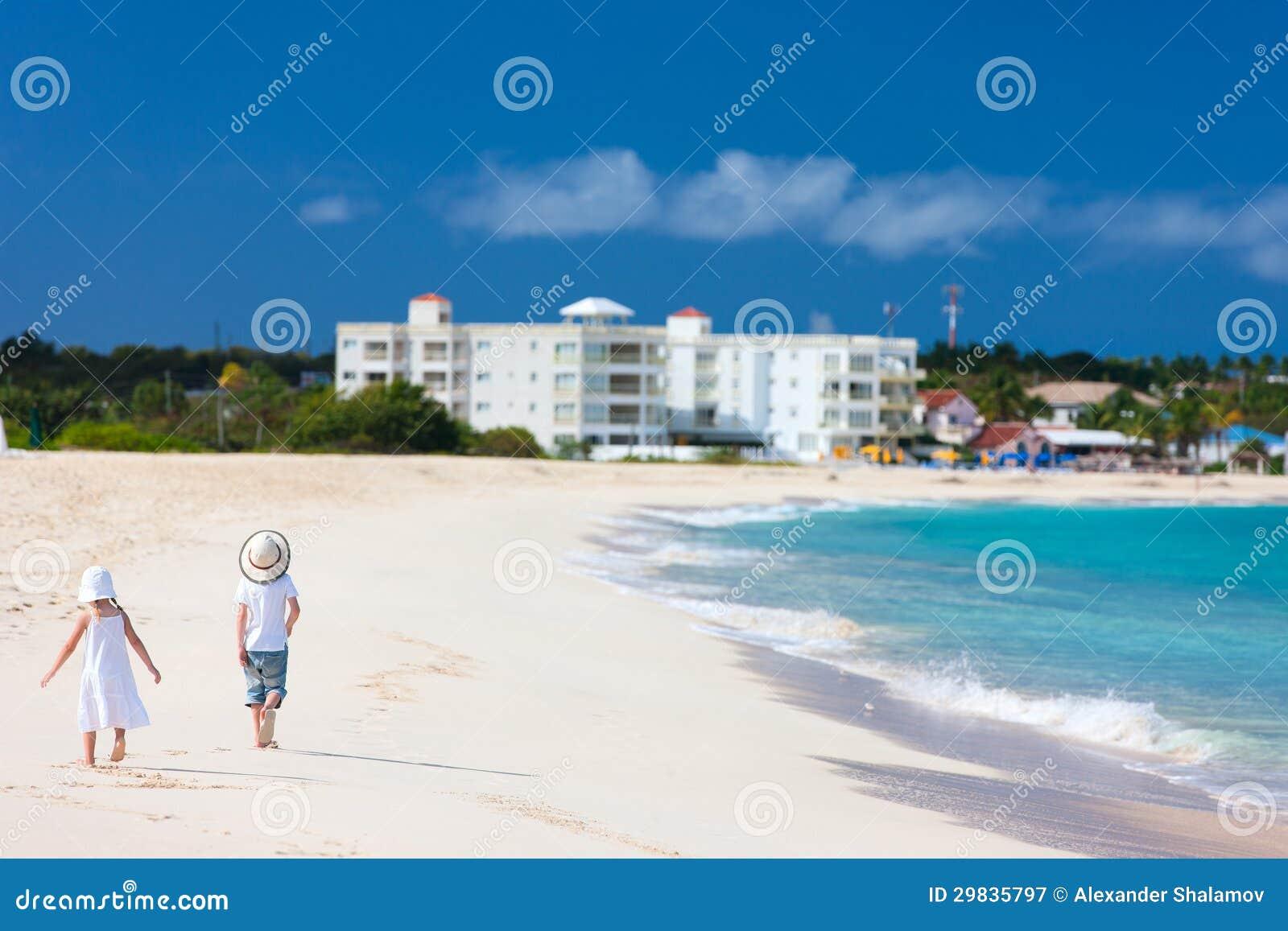Dois miúdos que andam ao longo de uma praia nas Caraíbas