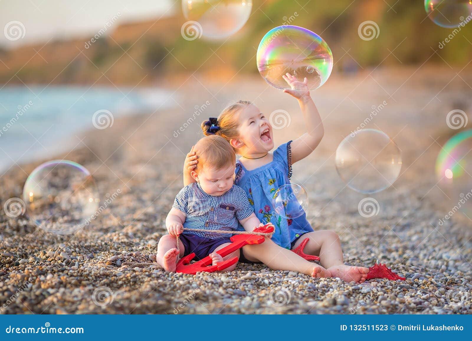 Irmão e irmã que jogam na ruptura da costa na praia durante o dia de férias quente do verão com bubles