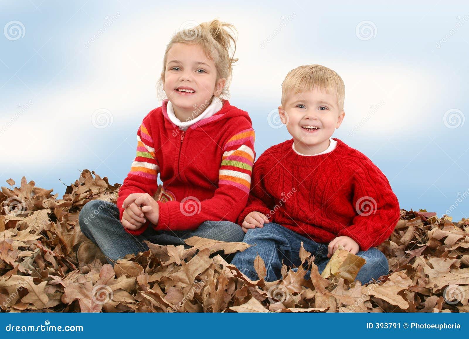 Irmão e irmã que sentam-se na pilha das folhas