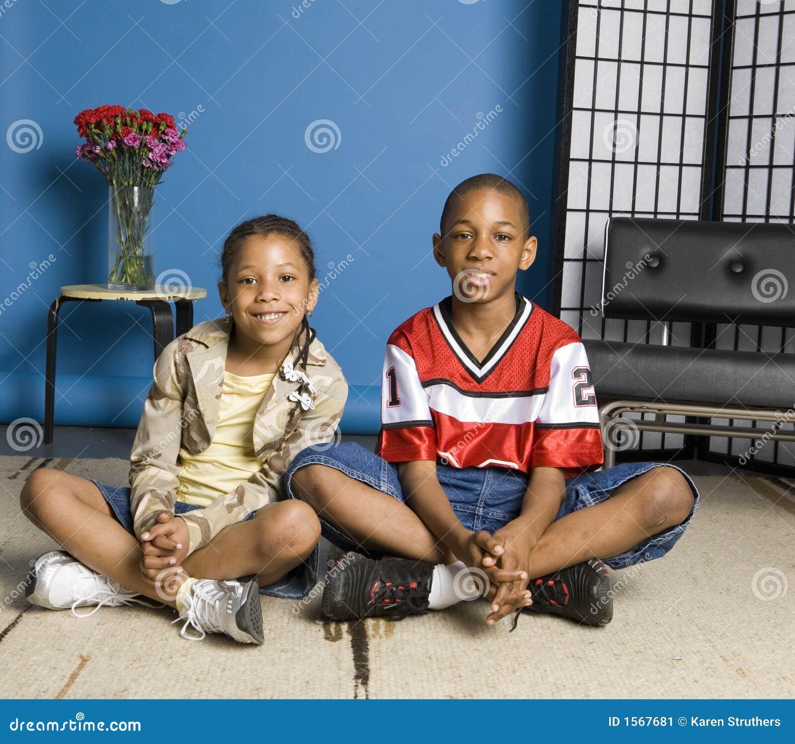 Irmão e irmã que sentam-se no assoalho