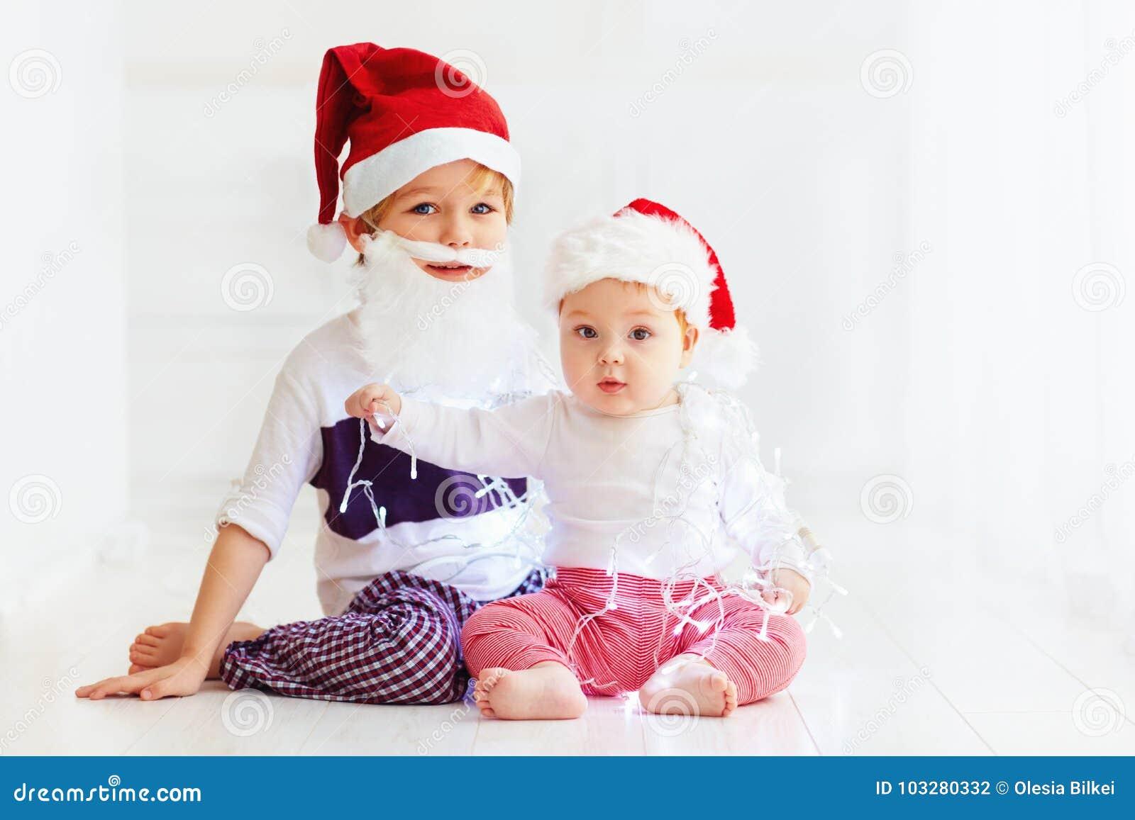 Irmãos bonitos do irmão, crianças em chapéus do ` s de Santa e festão que joga em casa