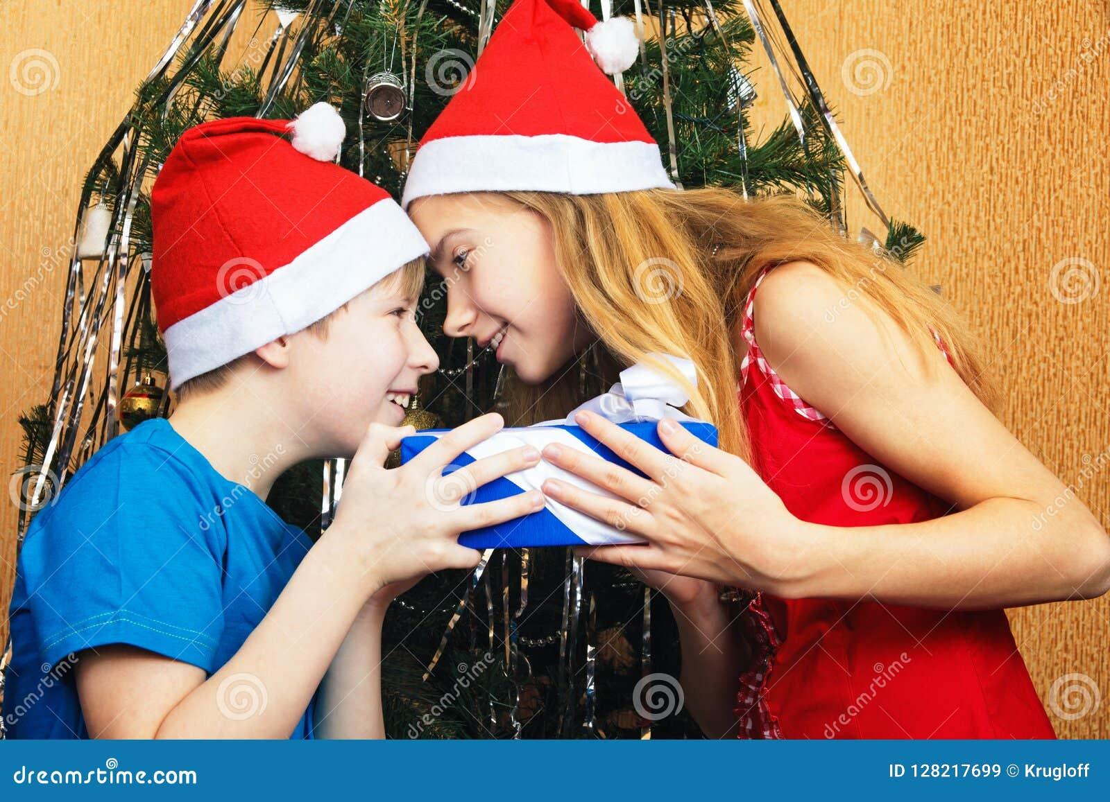 Irmãos dos adolescentes que tentam na brincadeira arrebatar-se presente do Natal do ` s