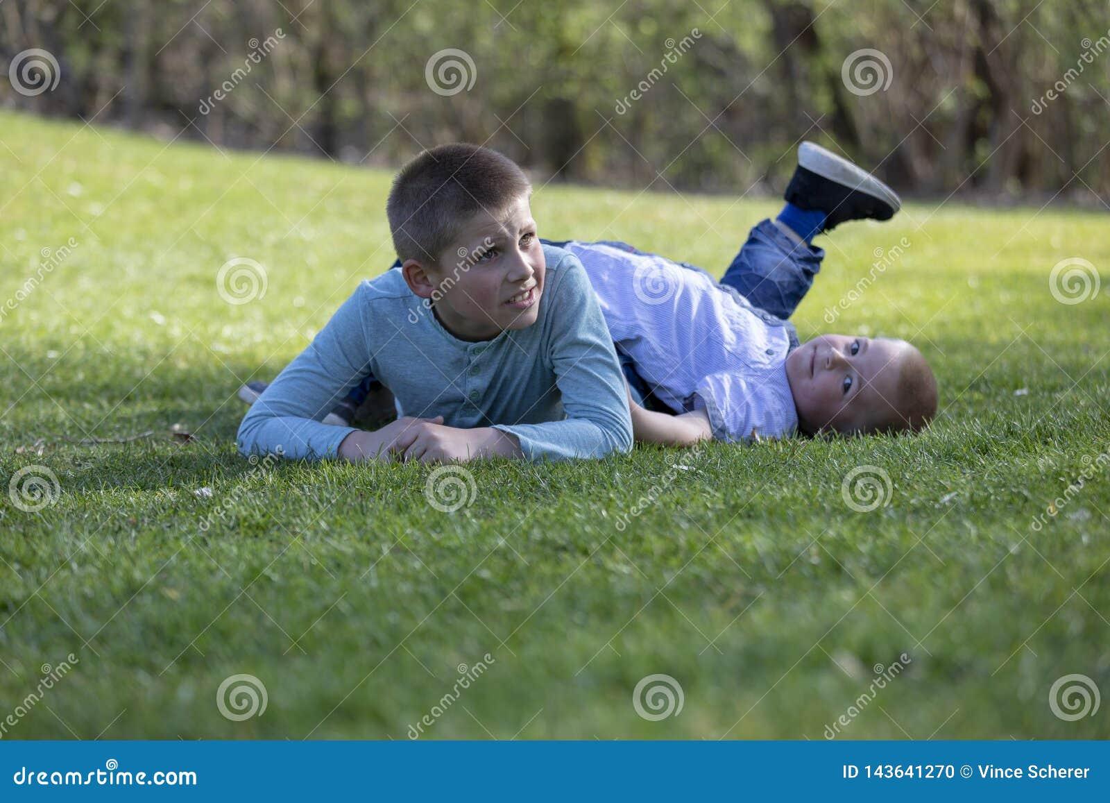 Irmãos que jogam na grama no verão