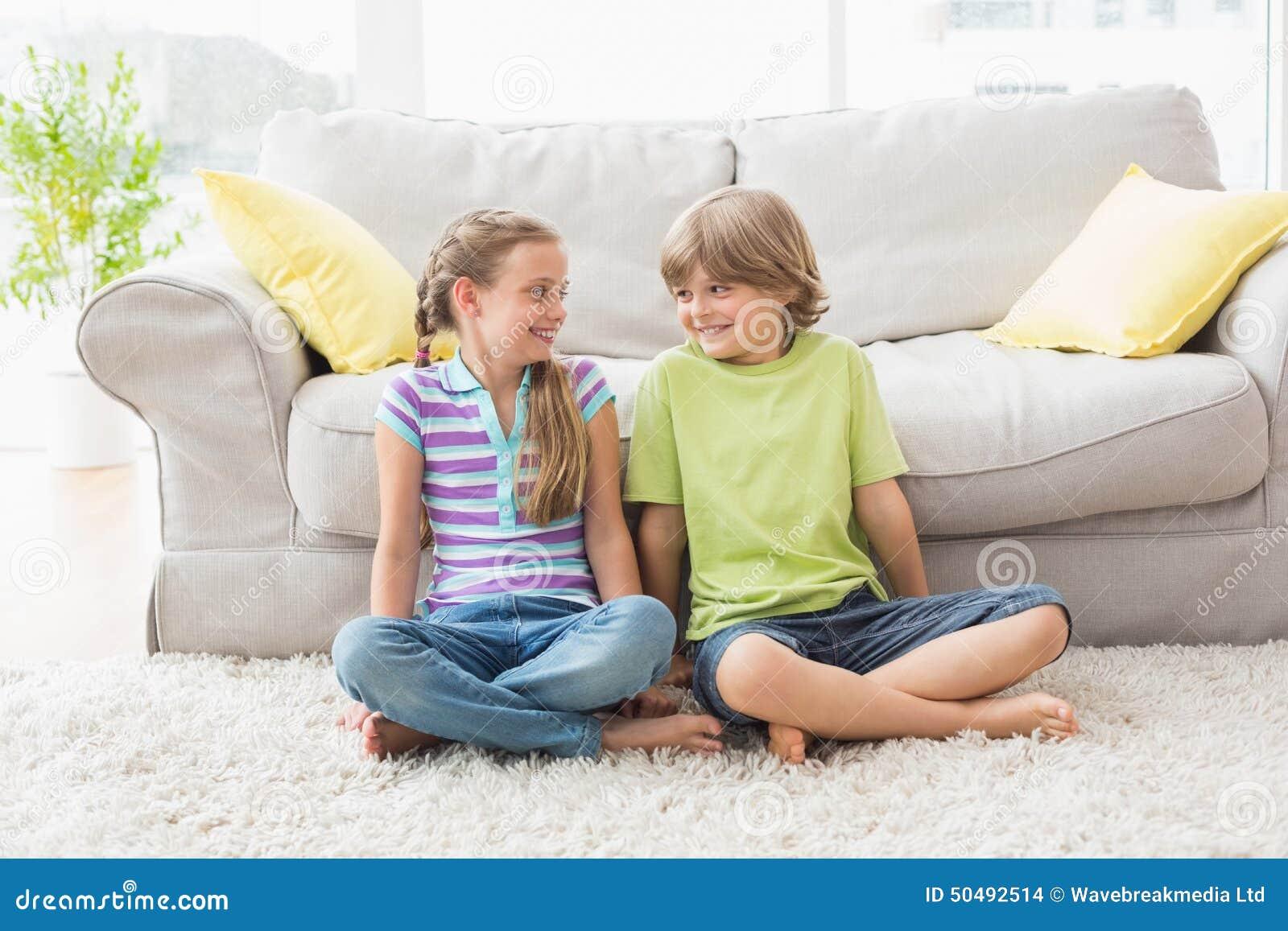 Irmãos que olham se ao sentar-se na sala do liviung