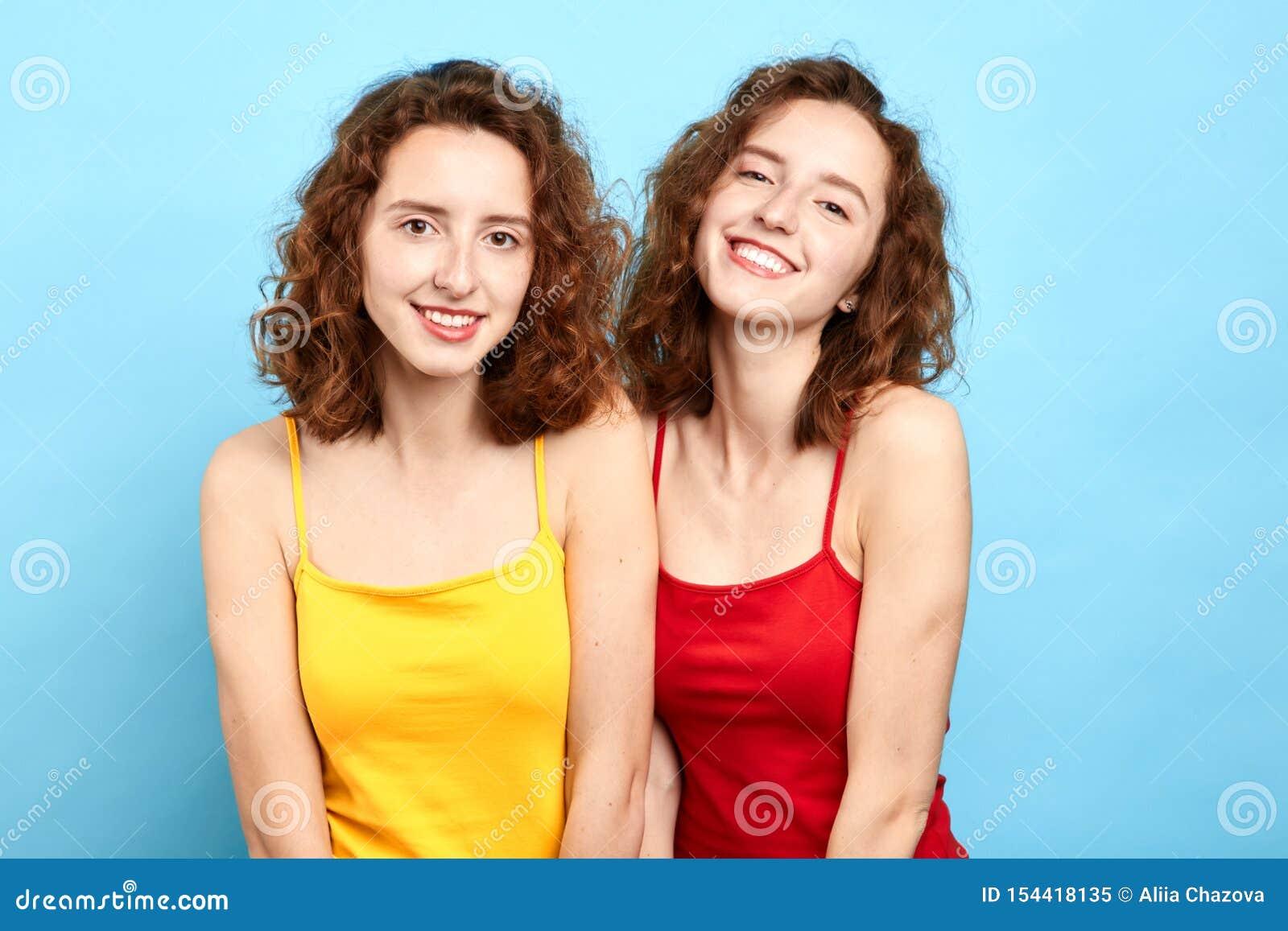 Irmãs gêmeas de sorriso que levantam à câmera isolada no azul