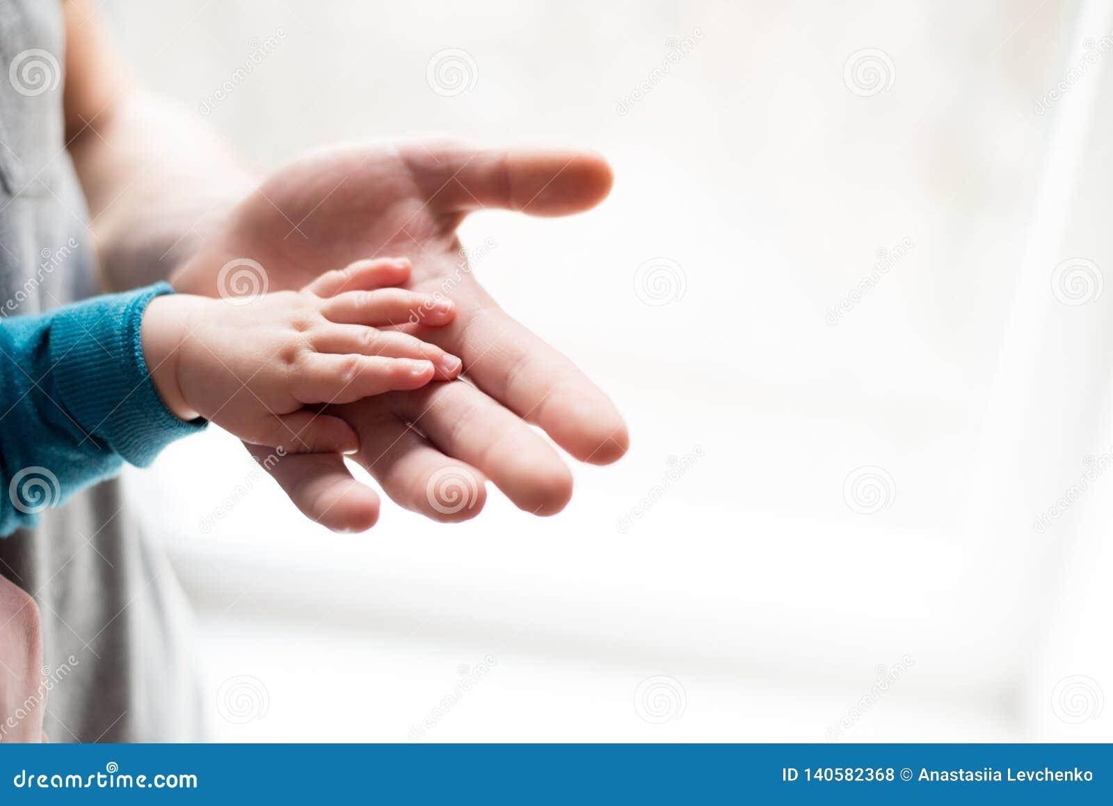 Irmãs que prendem as mãos entregue o bebê de sono na mão do close-up do pai Mãos no fundo branco