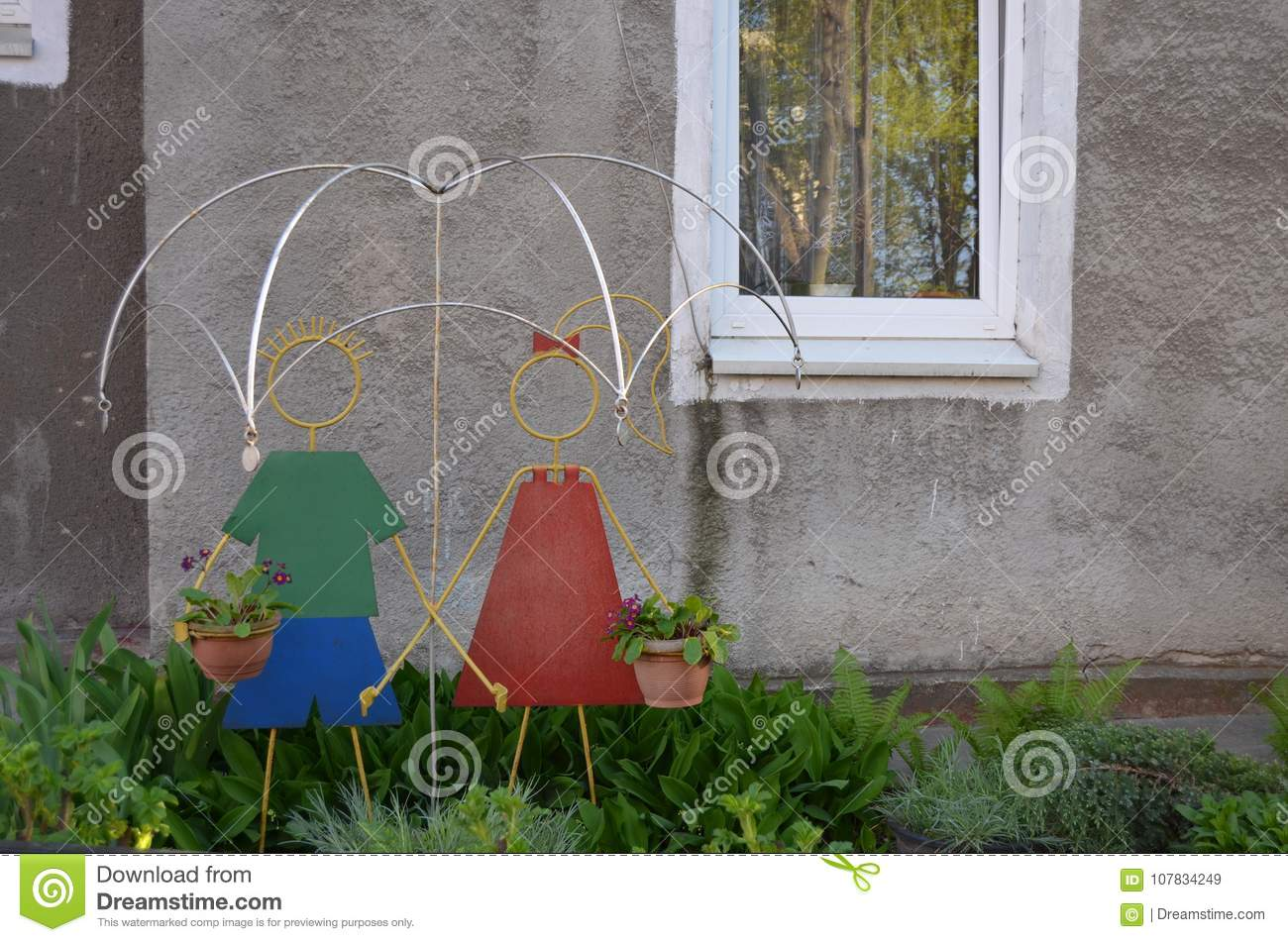 Iron Colored Figures Of A Boy And Girls With An Umbrella Stand In