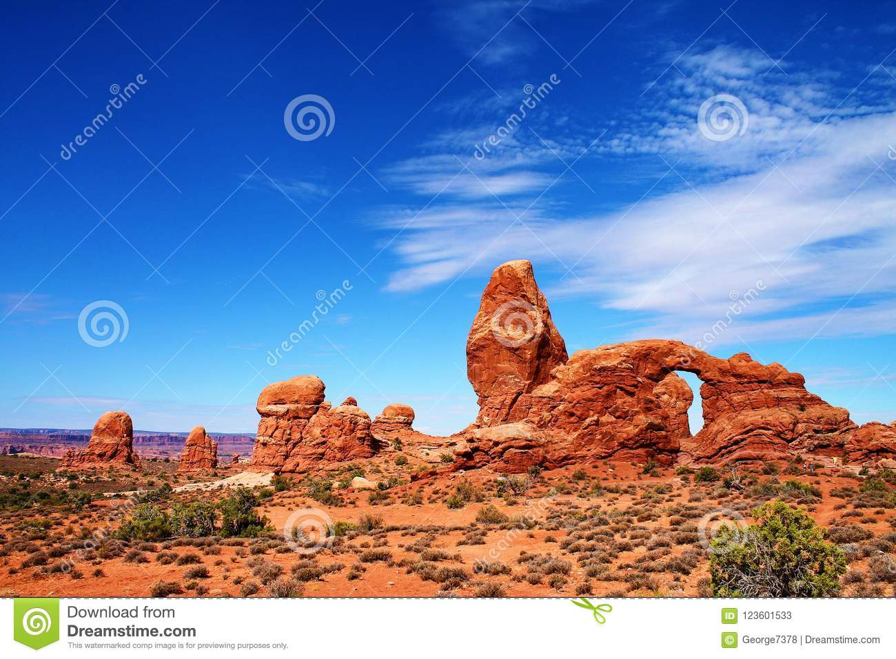 Irregular rock formations with pinnacles and arch, across a desert landscape in Utah