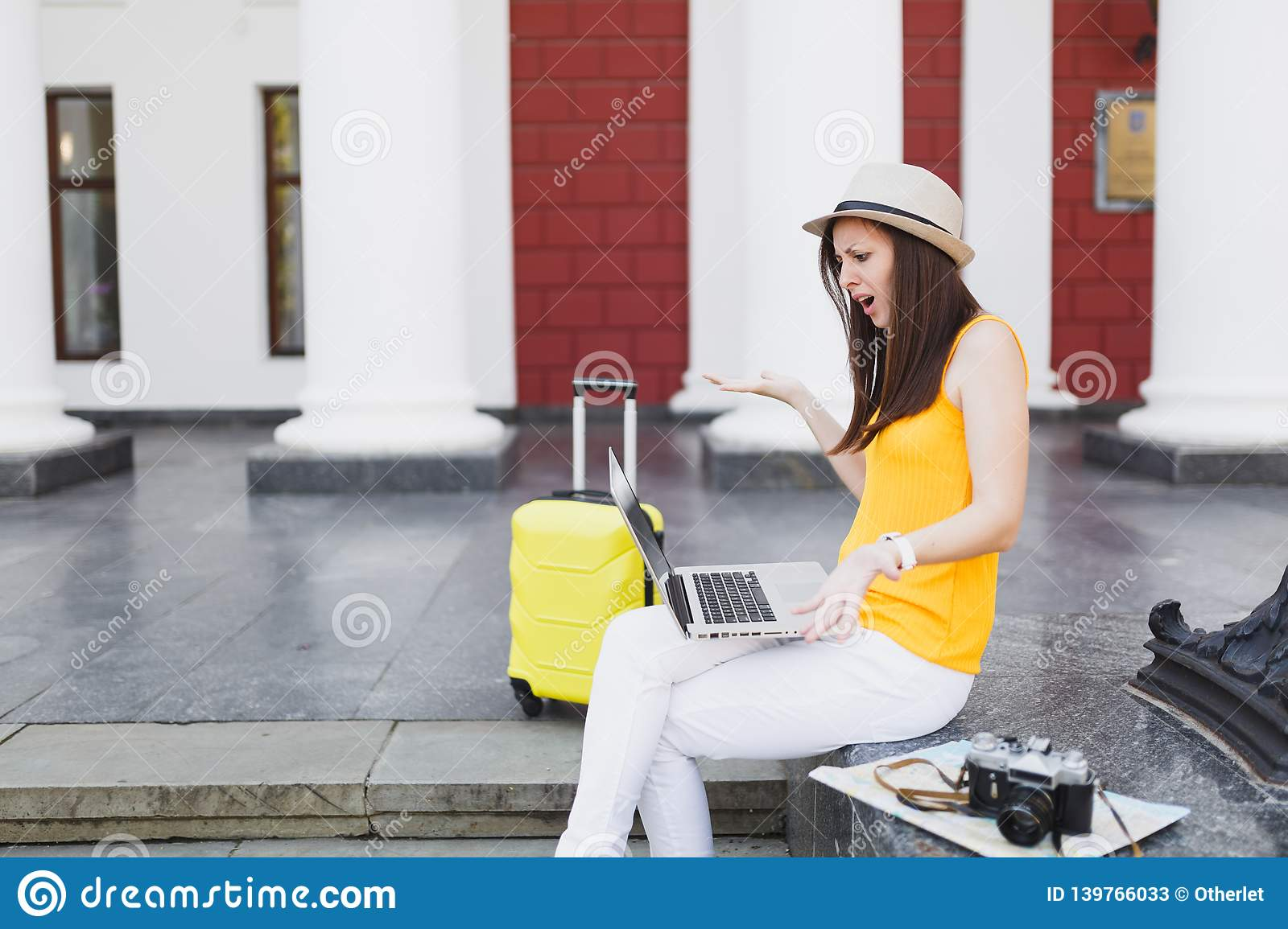 Irritated traveler tourist woman with suitcase sit on stairs using working on laptop pc computer spreading hands outdoor