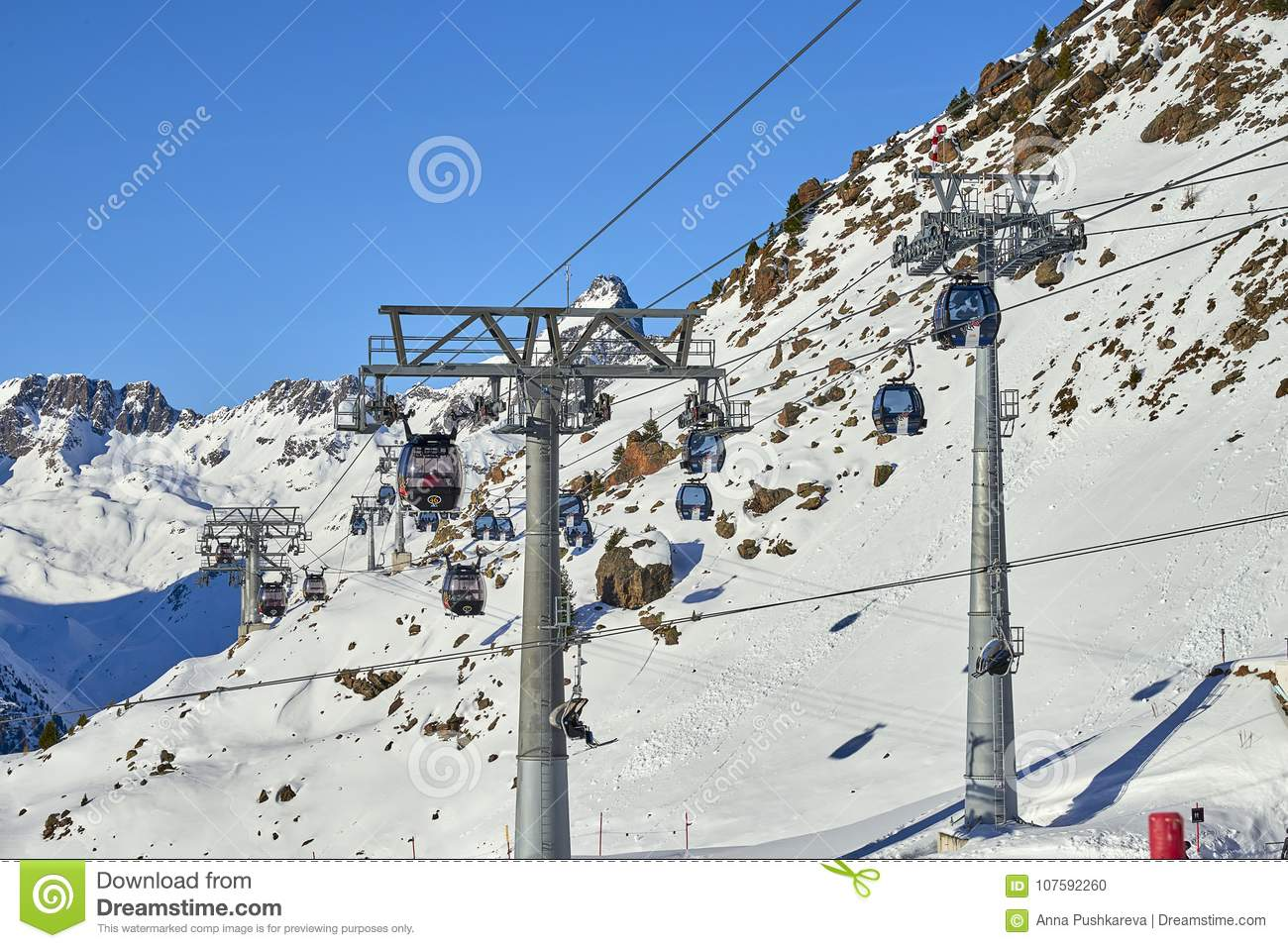Two links of mono-cable detachable gondolas with high transport capacity lift skiers to the hill top in Tyrol Alps in sunny Decemb
