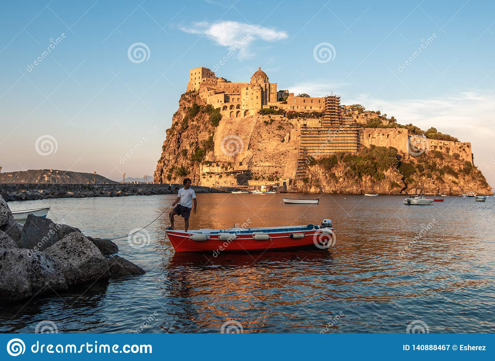 Ischia, Italië 20 Juni, 2017: Boatman met een boot op de achtergrond van het Aragonese-kasteel