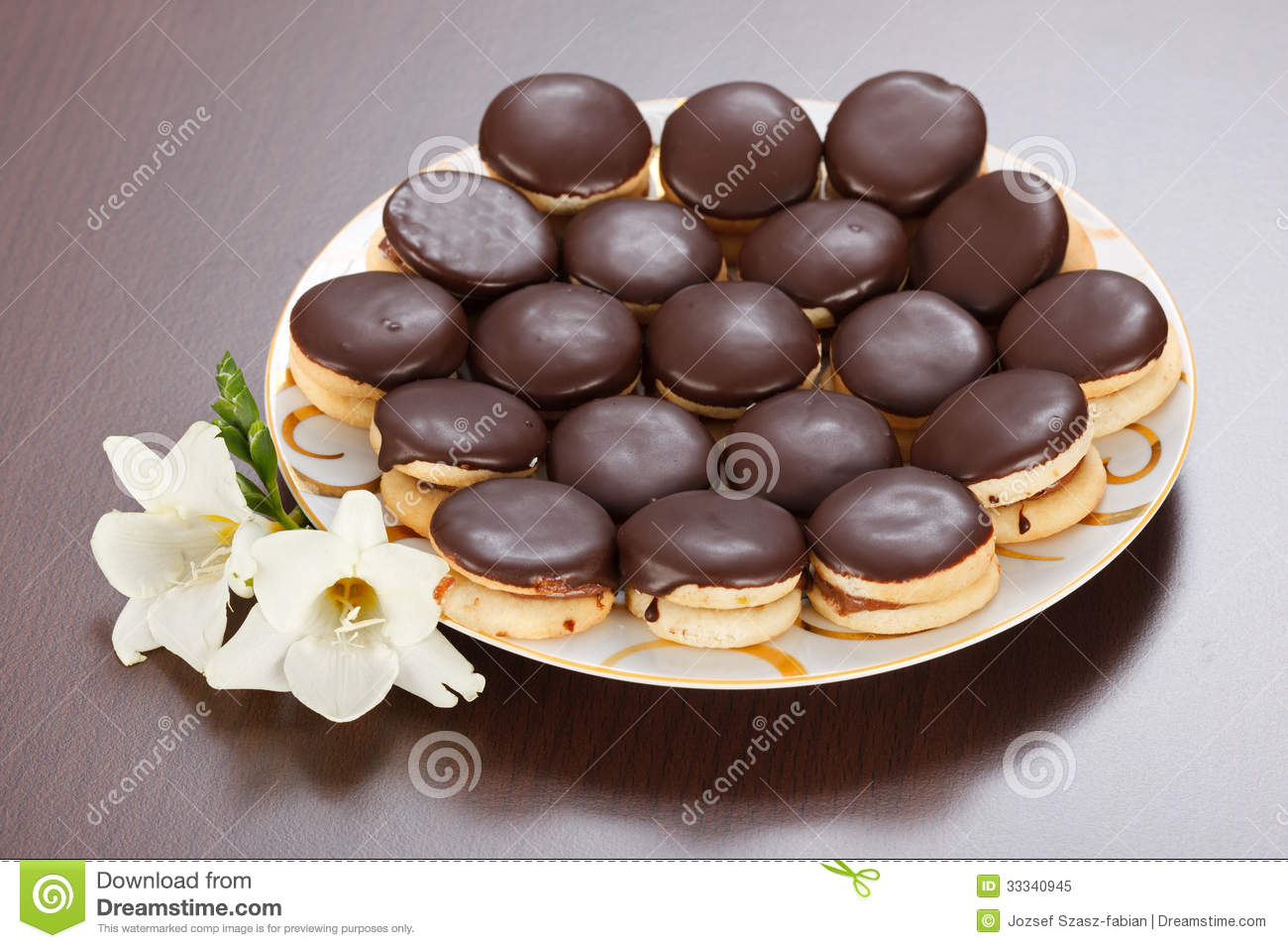 Ischler cookies coated with dark chocolate glaze on plate.