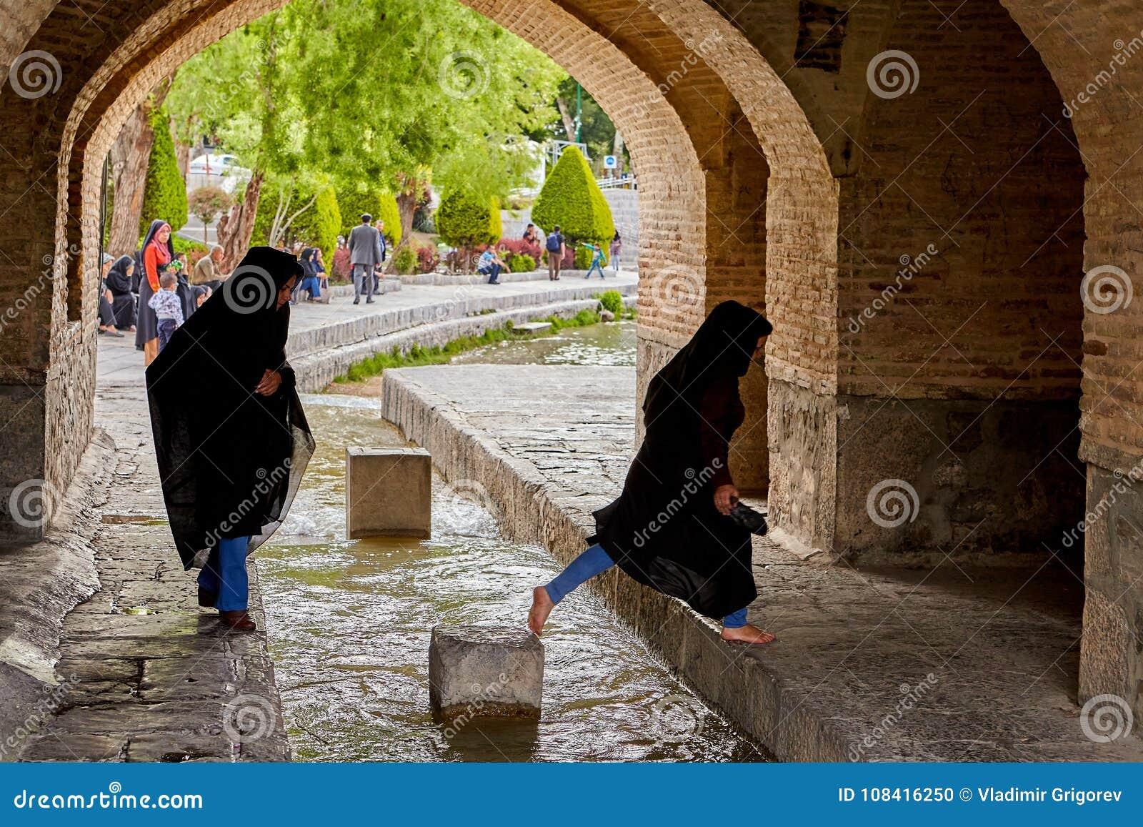 1dfefacb5190 Iranian Girls Step Over Flow Of Water Under Bridge