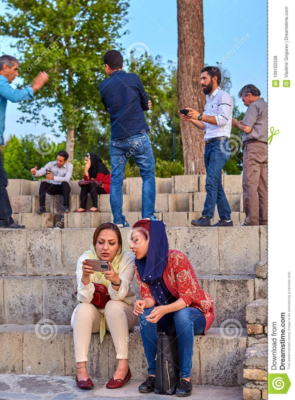 85d4c5515bef Young Iranian Women Are Browsing Photos On Smartphone