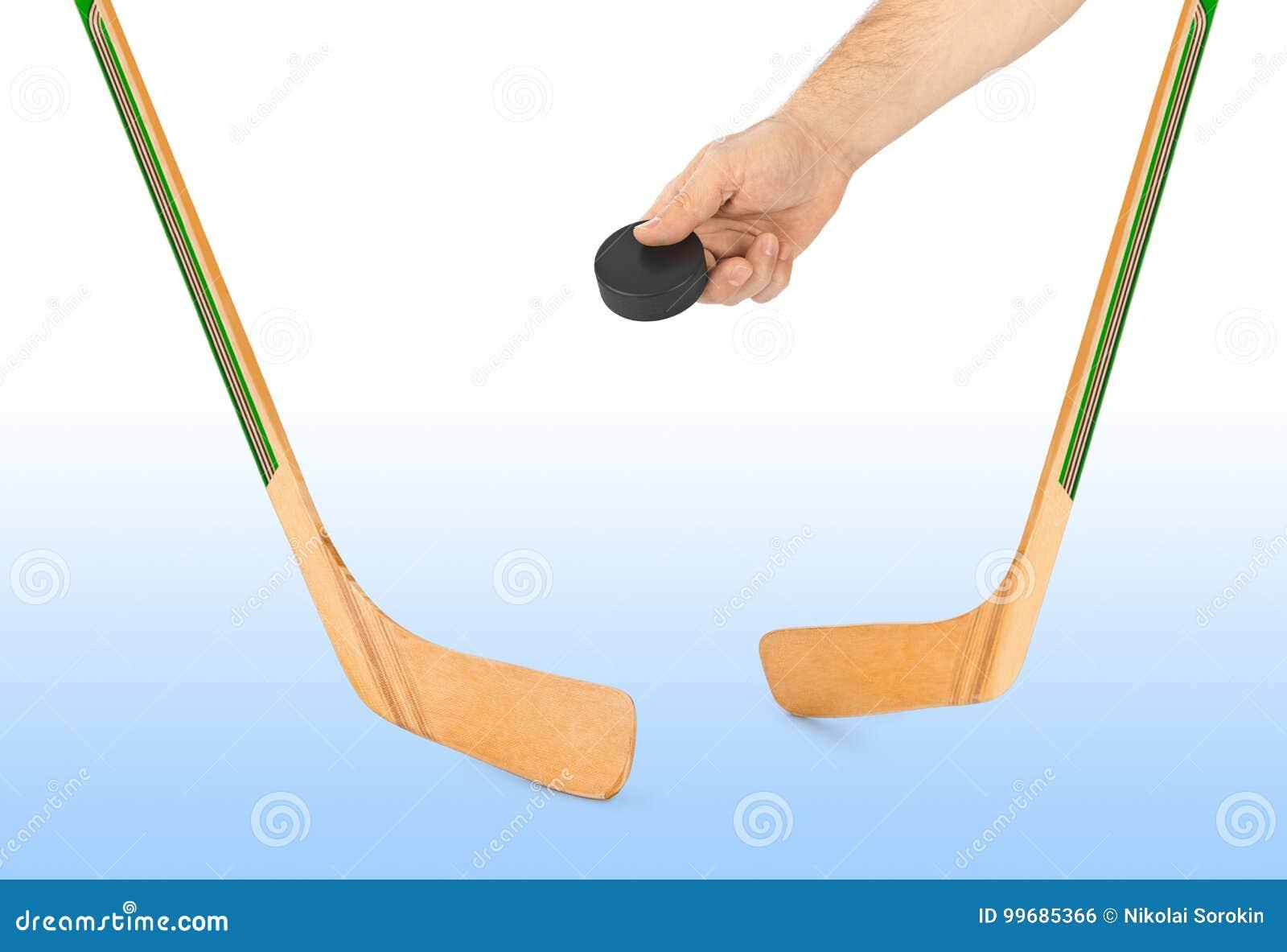 Ishockeypinne och hand med pucken