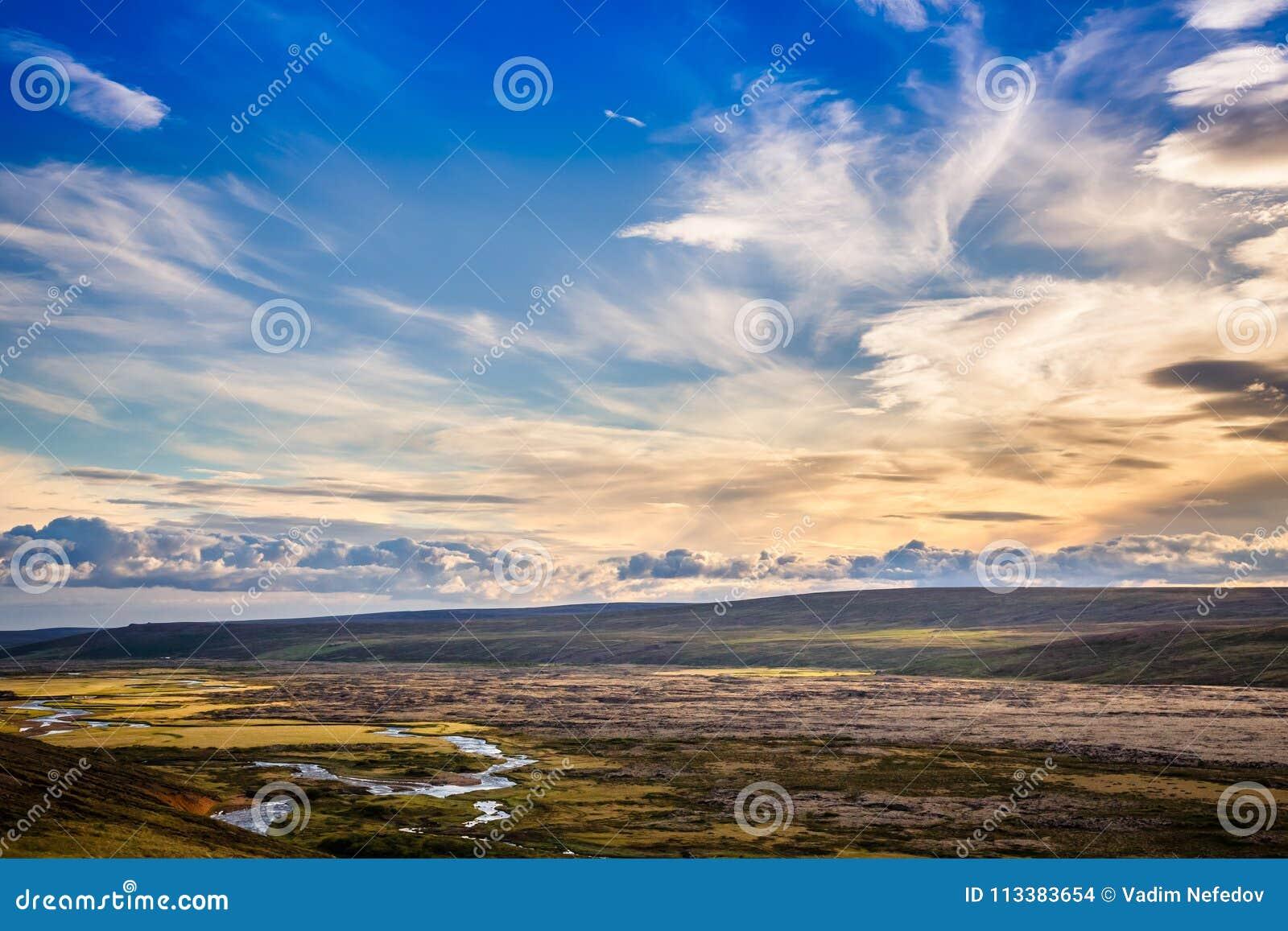 Isländisches ländliches Panorama mit grauen Wolken, grüne Felder, Hügel a