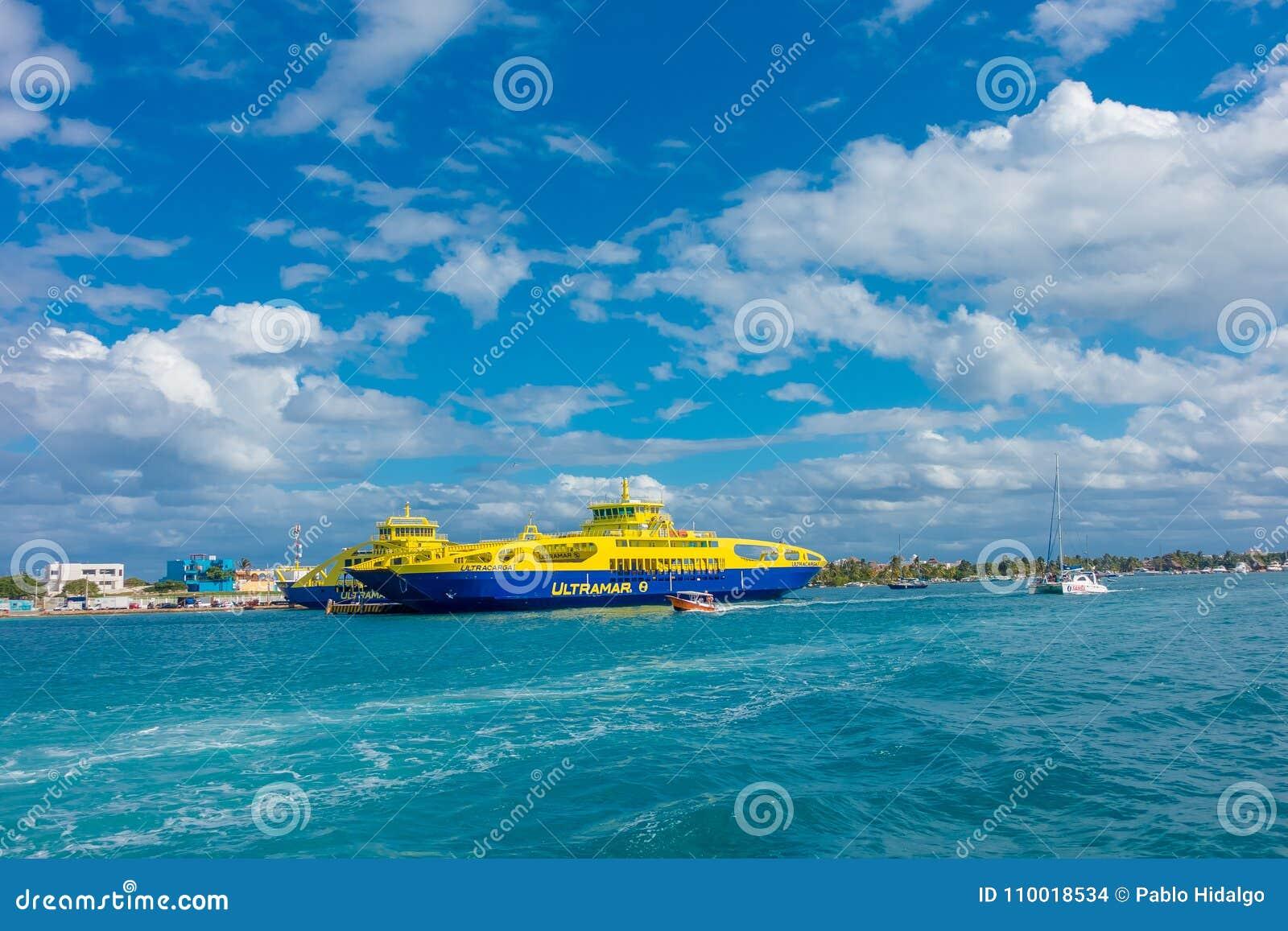 ISLA MUJERES, MEXICO, 10 JANUARI, 2018: Openluchtmening van reusachtige boot van kleur het blauwe en gele dicht varen in de water