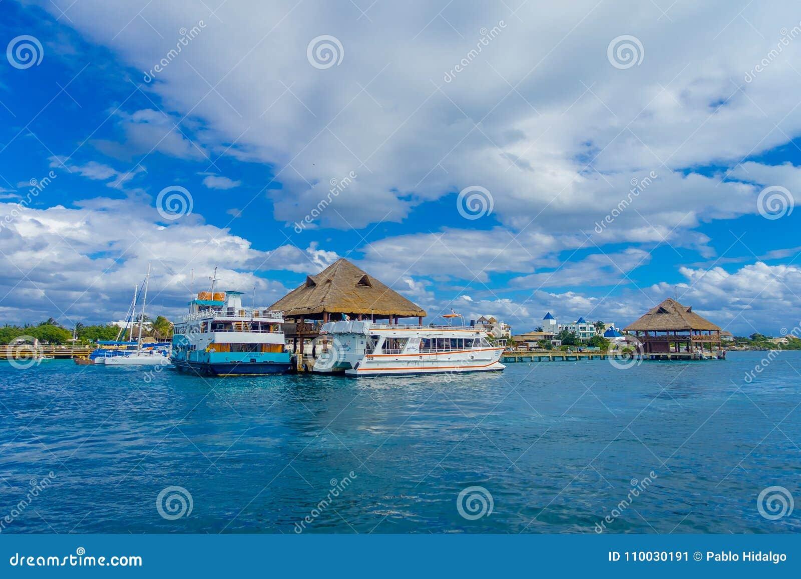 ISLA MUJERES, MEXICO, 10 JANUARI, 2018: Openluchtmening van schip in de kust met vele passagier, dicht bij een typisch huis