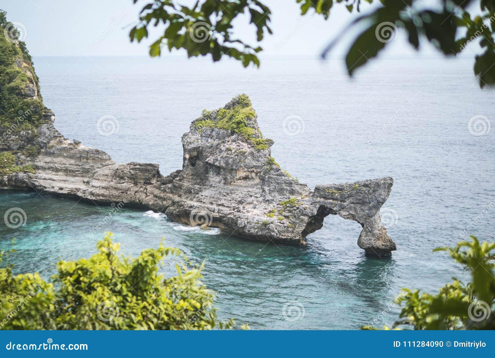 Isla natural hermosa del arco de la roca en el mar en la playa de Atuh en Nusa Penida, Bali, Indonesia Silueta del hombre de nego