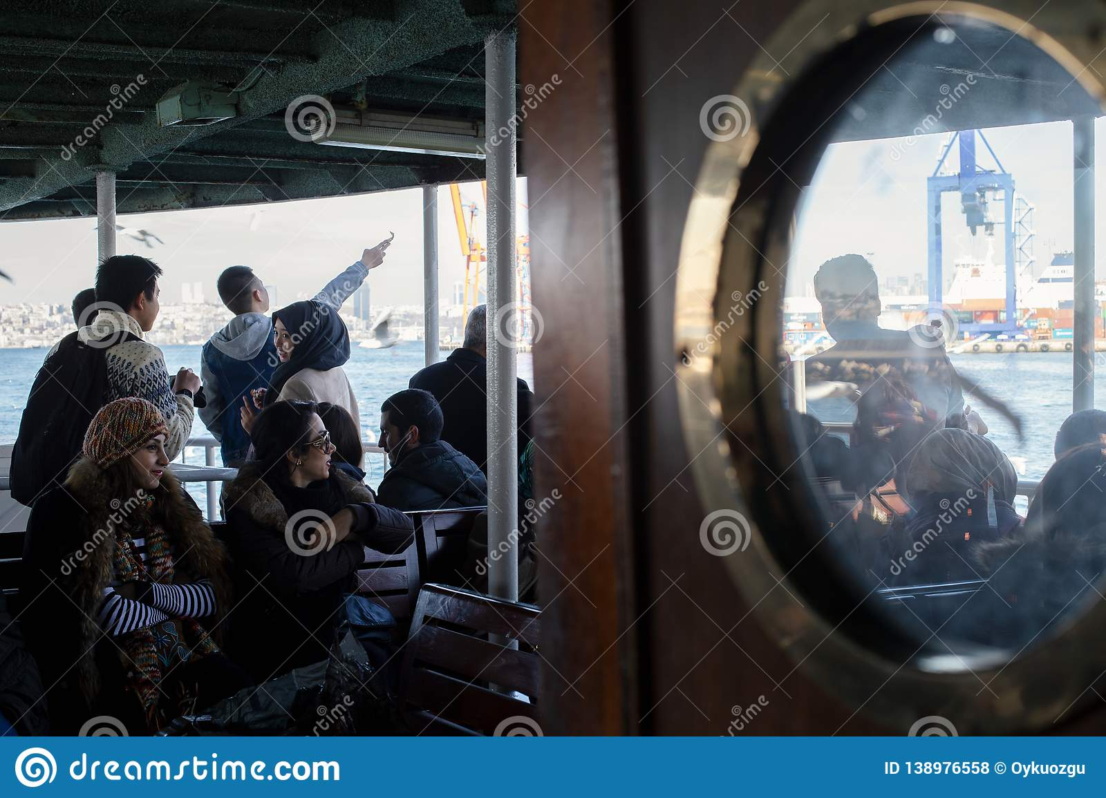 Island Ferry Ada Vapuru. Some of the ferry passengers feed seagulls. Passenger ferryboats from Istanbul sail regularly to the Pr. Istanbul / Turkey - 02/03/2016 royalty free stock photos